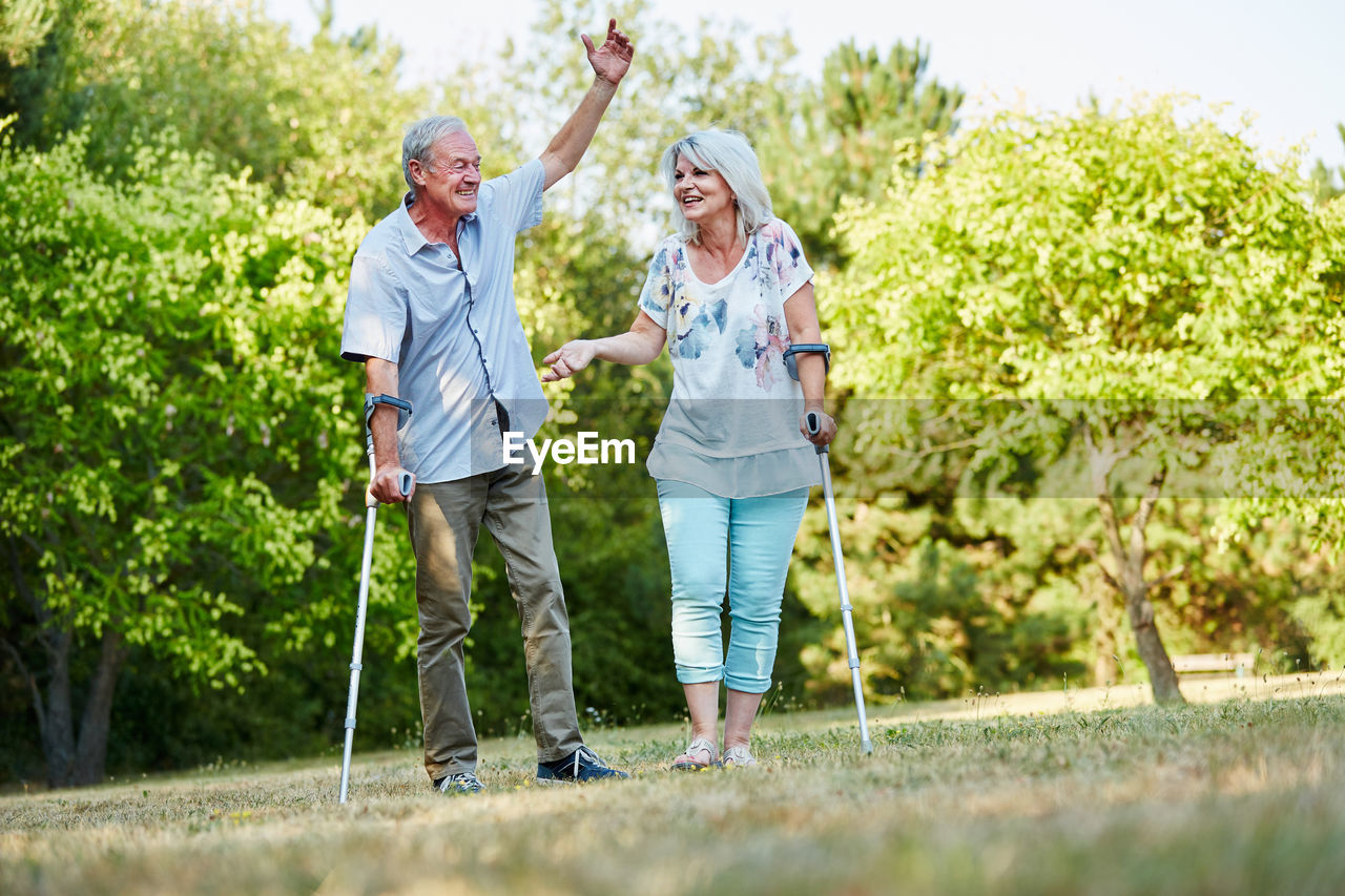 Couple With Crutches Walking In Park