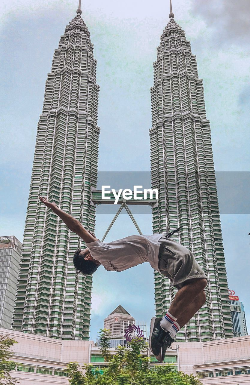 architecture, built structure, building exterior, tall - high, one person, building, skyscraper, office building exterior, city, real people, low angle view, office, sky, day, lifestyles, tower, modern, nature, men, outdoors