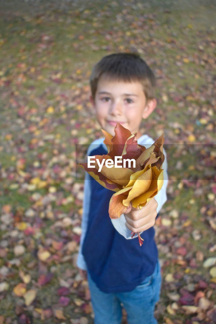 Portrait Of Boy Holding Leaves