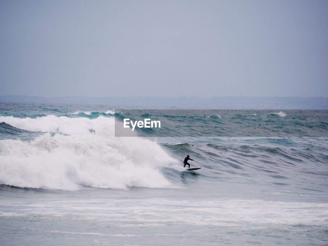 sport, sea, motion, aquatic sport, water, wave, sky, leisure activity, real people, surfing, one person, horizon over water, adventure, waterfront, lifestyles, horizon, skill, sports equipment, power in nature, outdoors