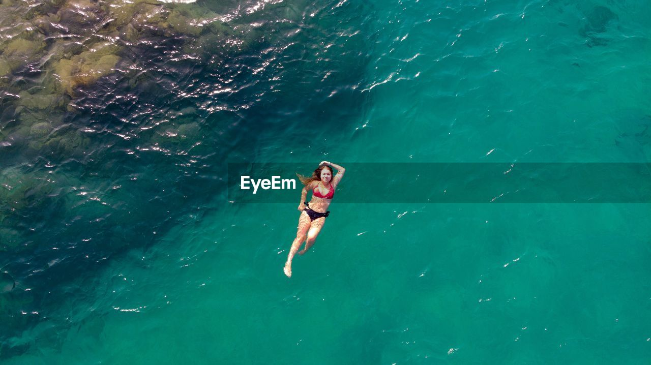 sea, water, leisure activity, one person, lifestyles, adventure, nature, swimwear, bikini, holiday, clothing, trip, real people, day, vacations, high angle view, sport, full length, outdoors, turquoise colored, snorkeling