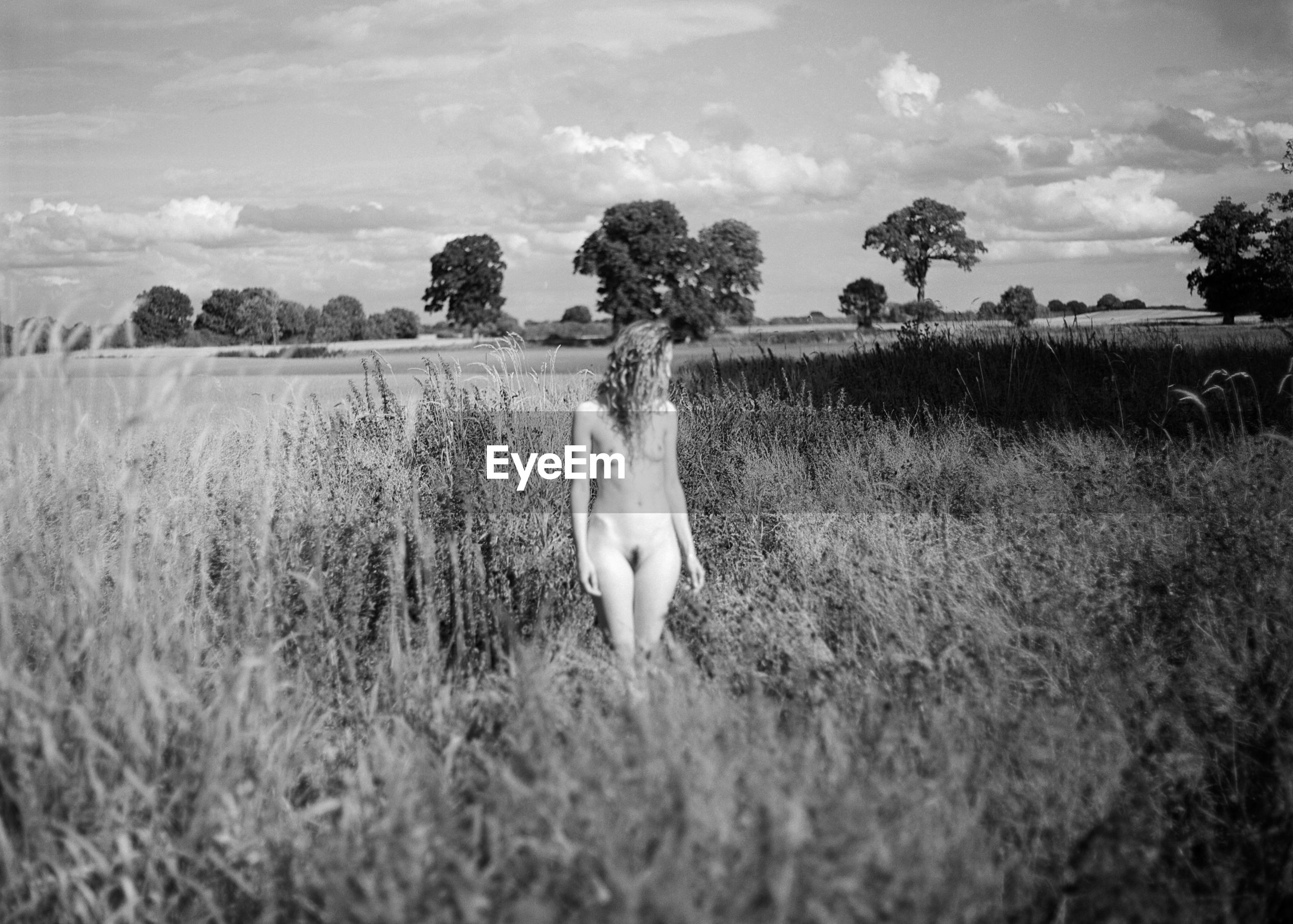 Naked woman standing on field against sky