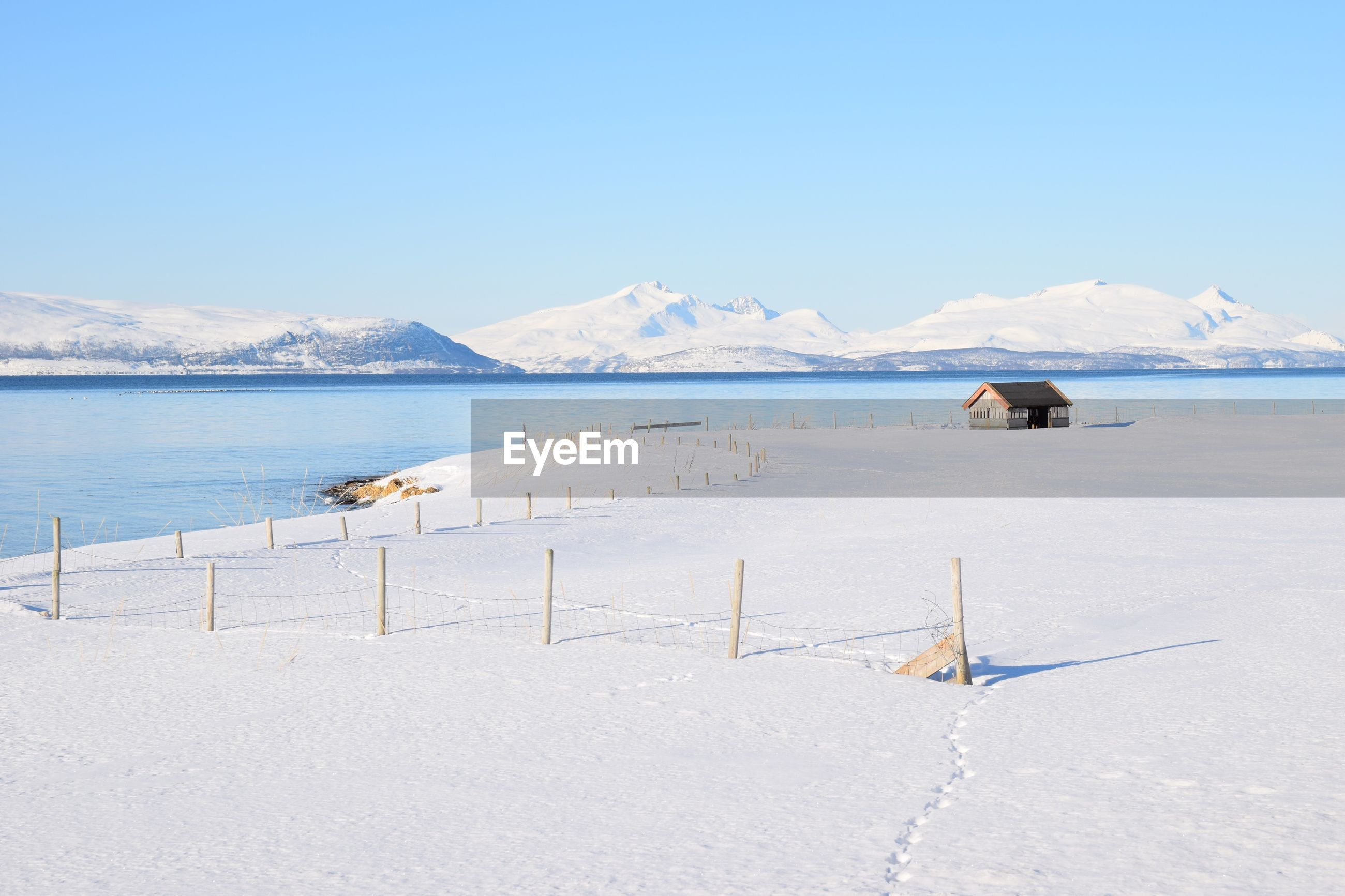 SCENIC VIEW OF SEA AGAINST SNOWCAPPED MOUNTAINS DURING WINTER
