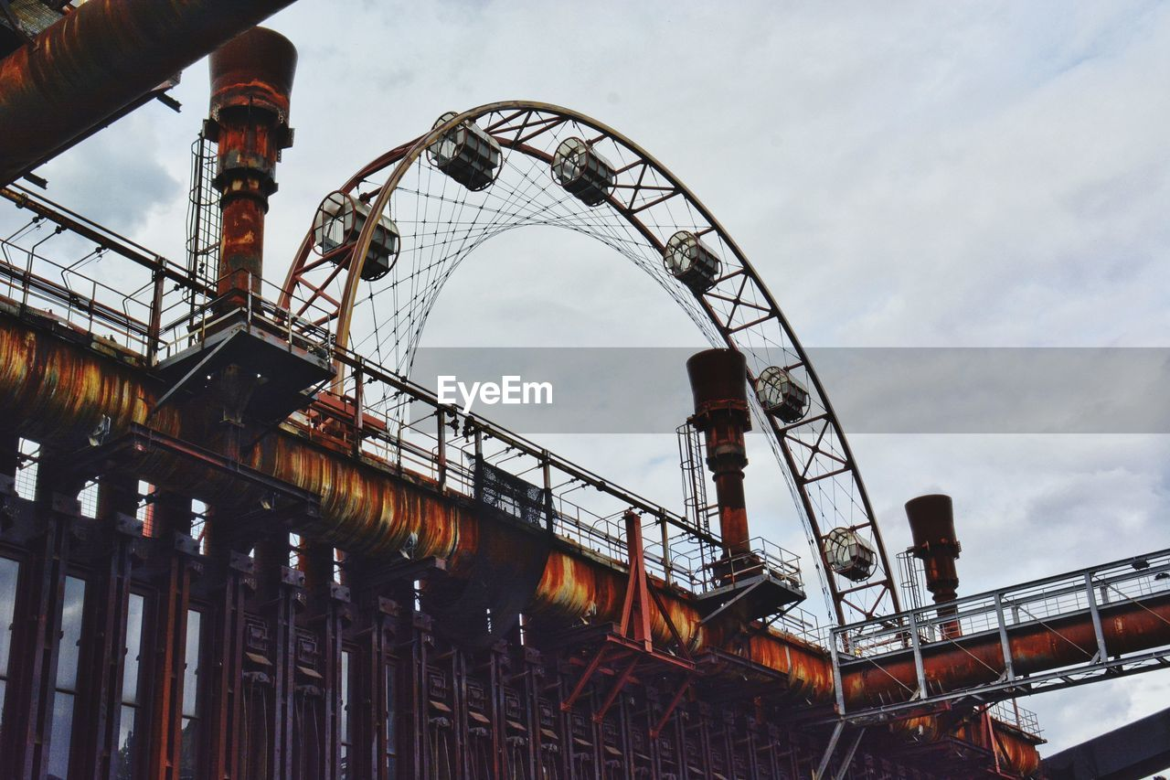 LOW ANGLE VIEW OF ROLLERCOASTER IN INDUSTRY AGAINST SKY