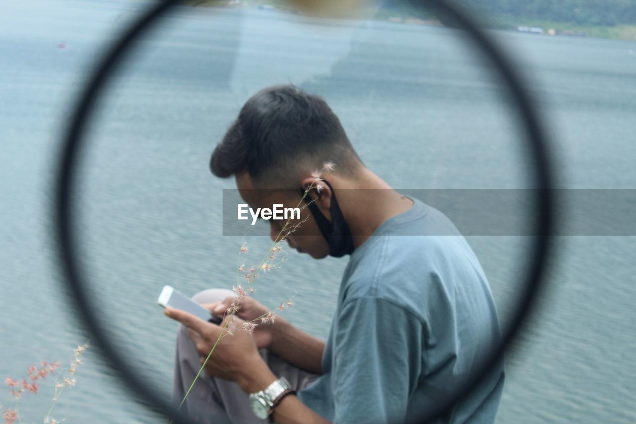 Full length portrait of man using mobile phone
