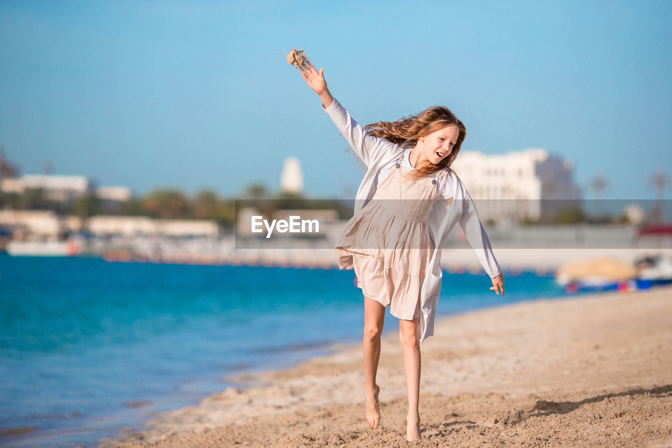 Happy girl with arms outstretched walking at beach against clear sky