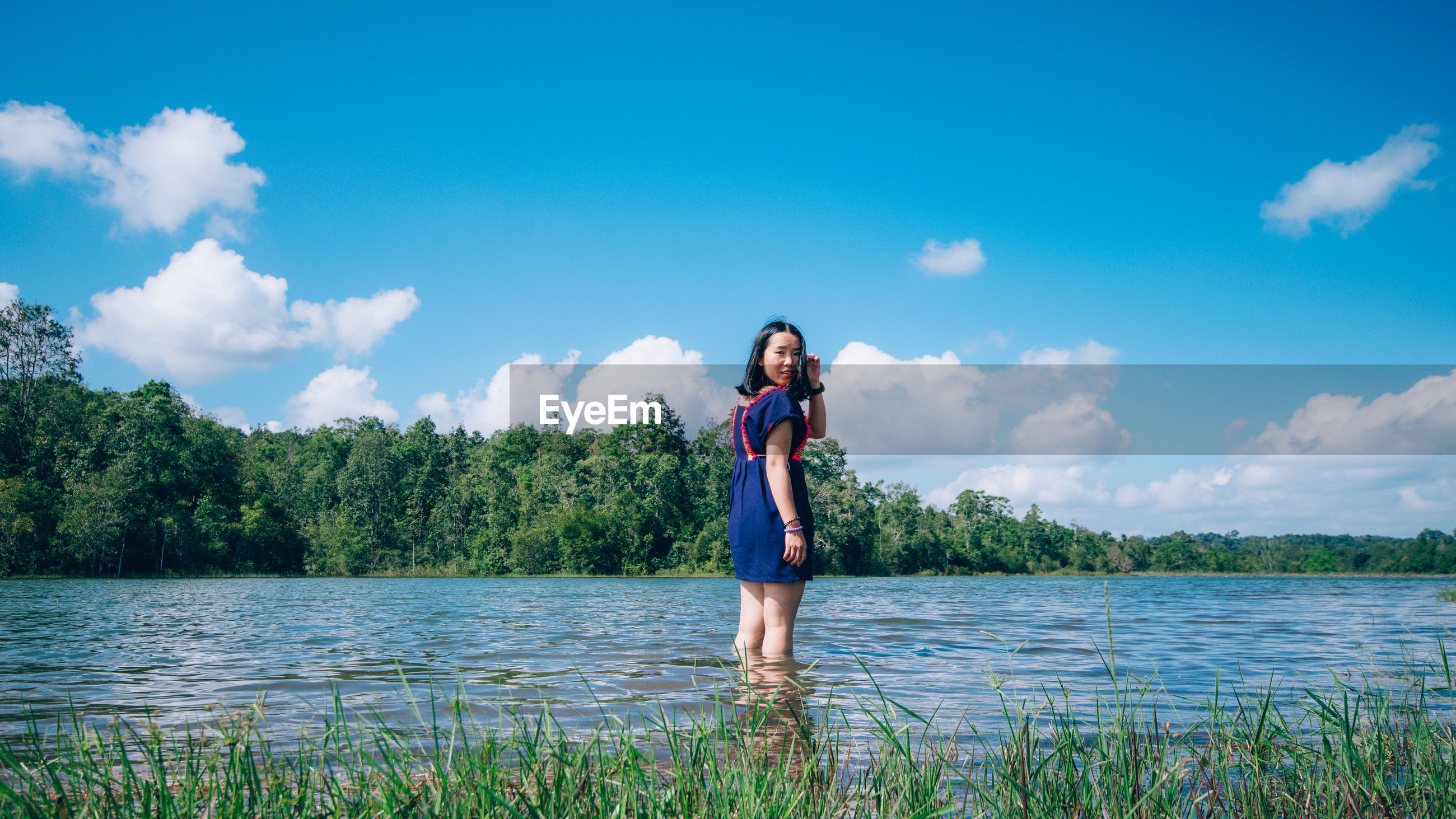 Young woman standing in lake against sky