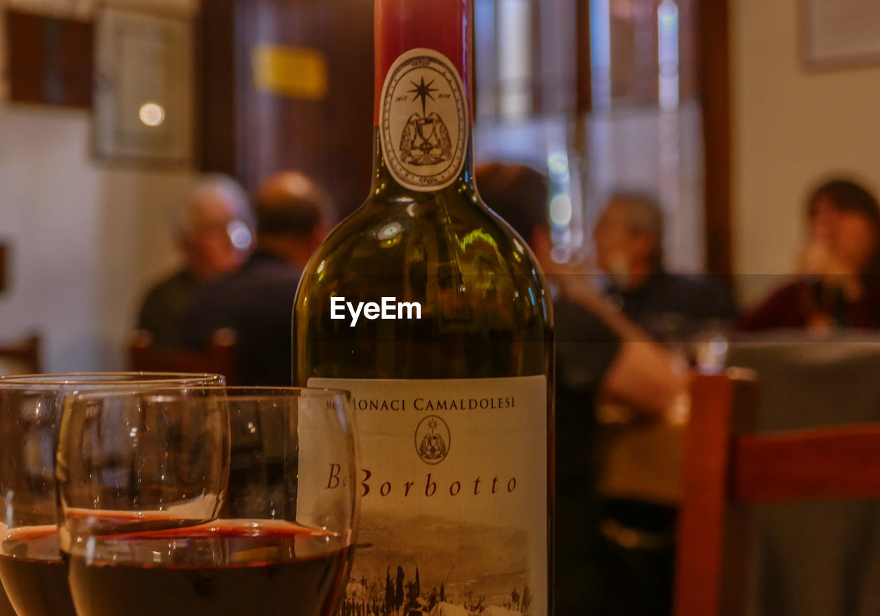 alcohol, food and drink, refreshment, text, bottle, drink, container, indoors, transparent, western script, glass - material, table, wine, incidental people, focus on foreground, communication, close-up, glass, restaurant, wine bottle, luxury