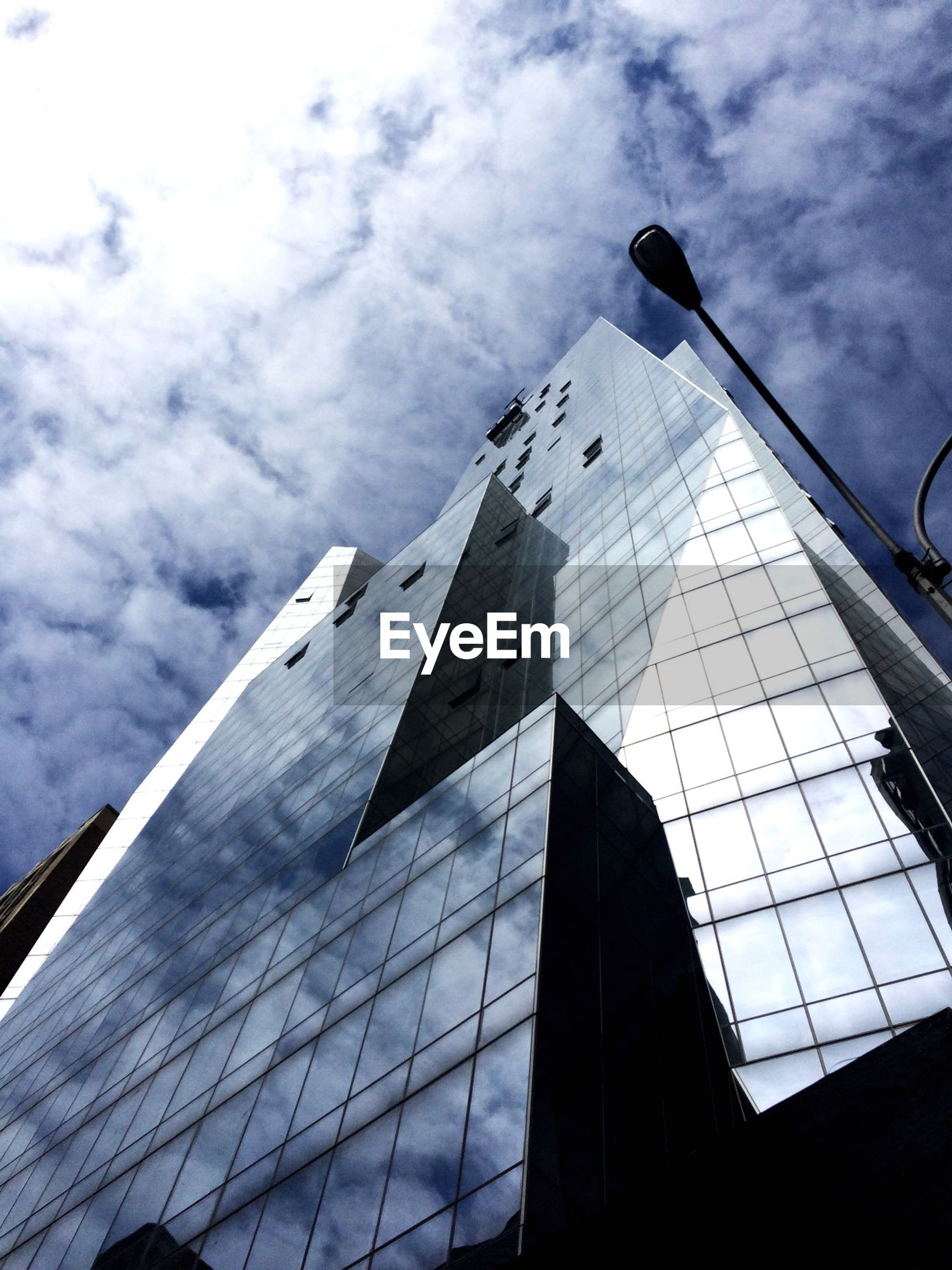 Low angle view of tall building against cloudy sky