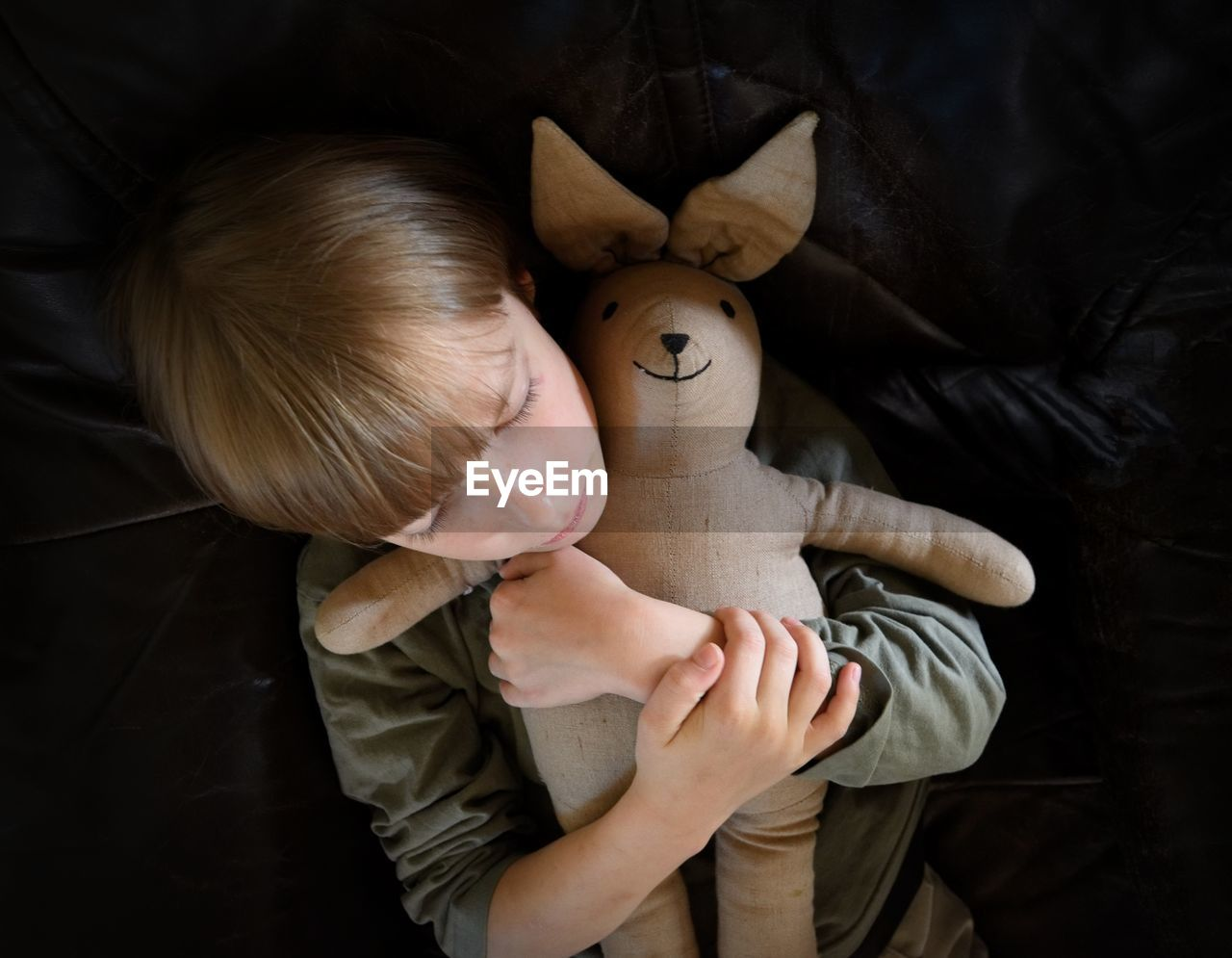 Directly Above Shot Of Boy Embracing Stuffed Toy While Lying On Bed
