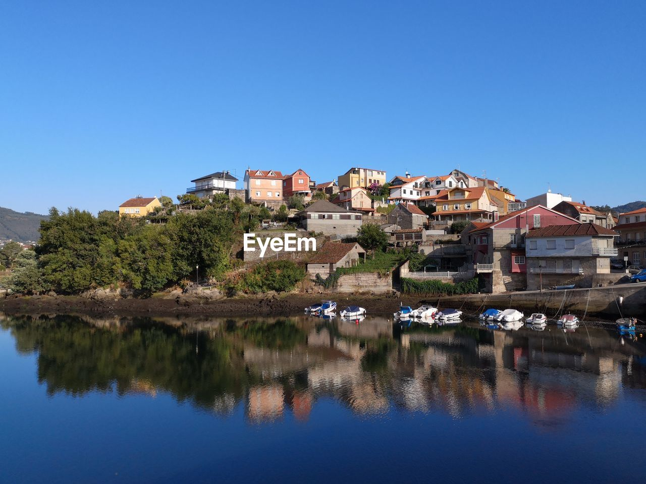 Scenic View Of Lake By Buildings Against Clear Blue Sky