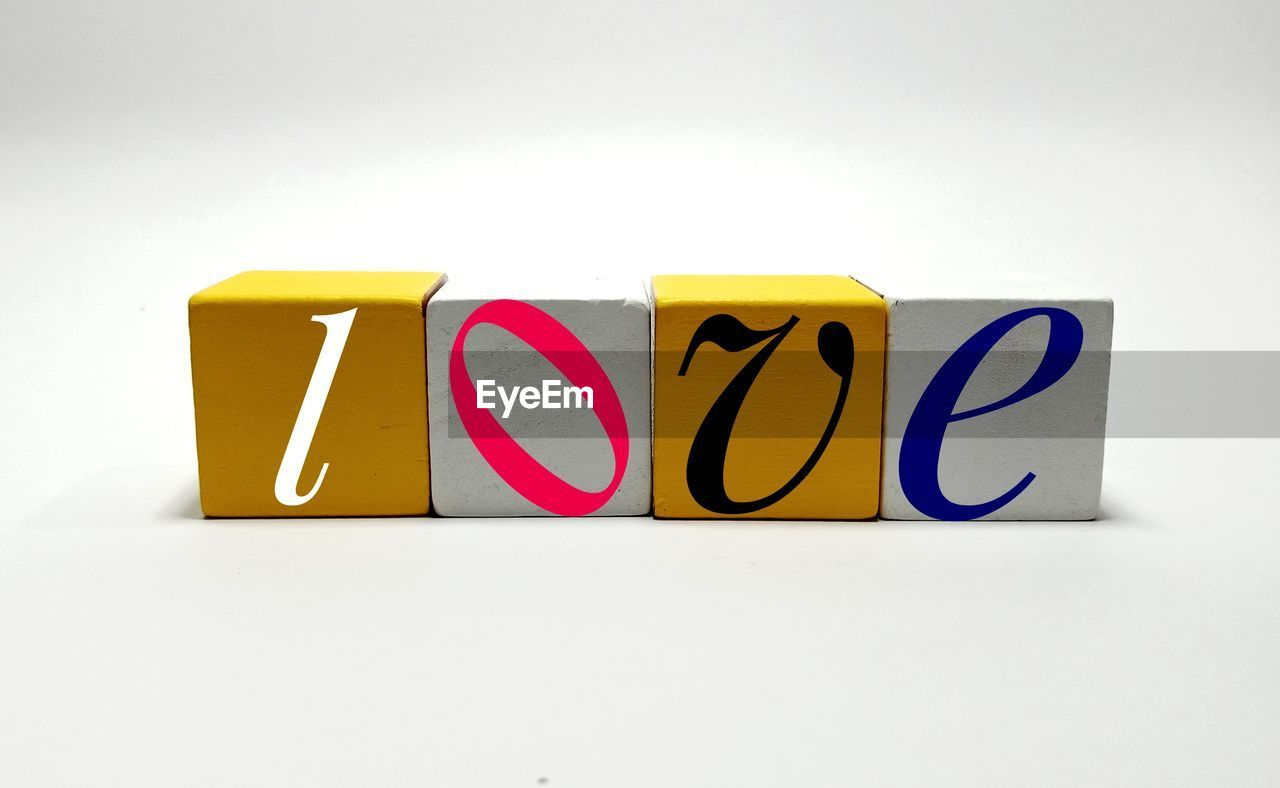 Close-up of love text made with toy blocks over white background