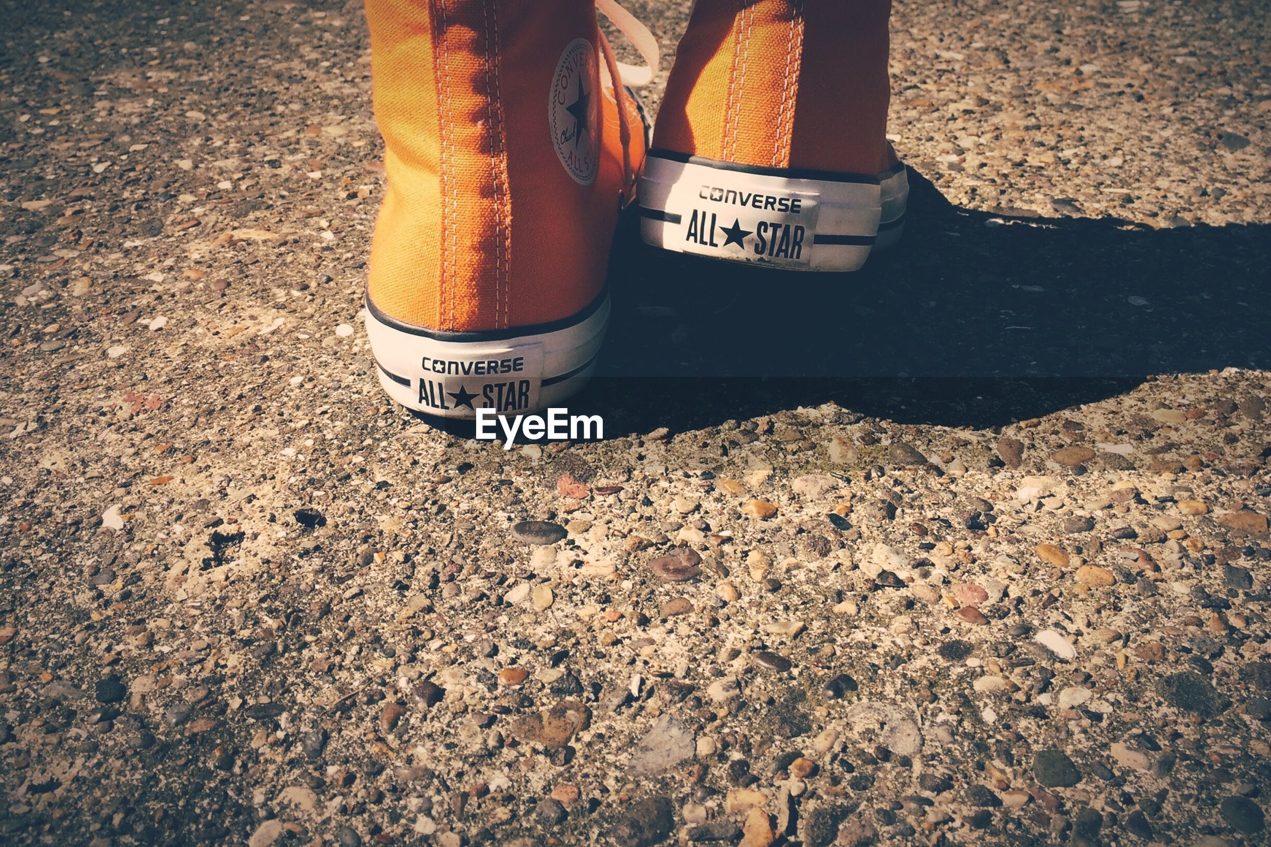 high angle view, text, communication, shoe, street, western script, low section, outdoors, day, non-western script, sunlight, person, yellow, road, close-up, sign, field, footwear, guidance