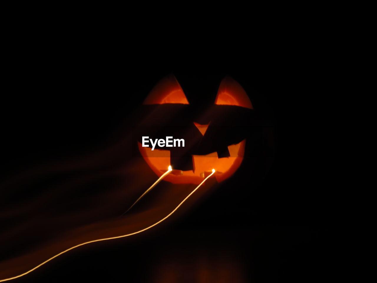 Close-Up Of Illuminated Jack O Lantern In Darkroom