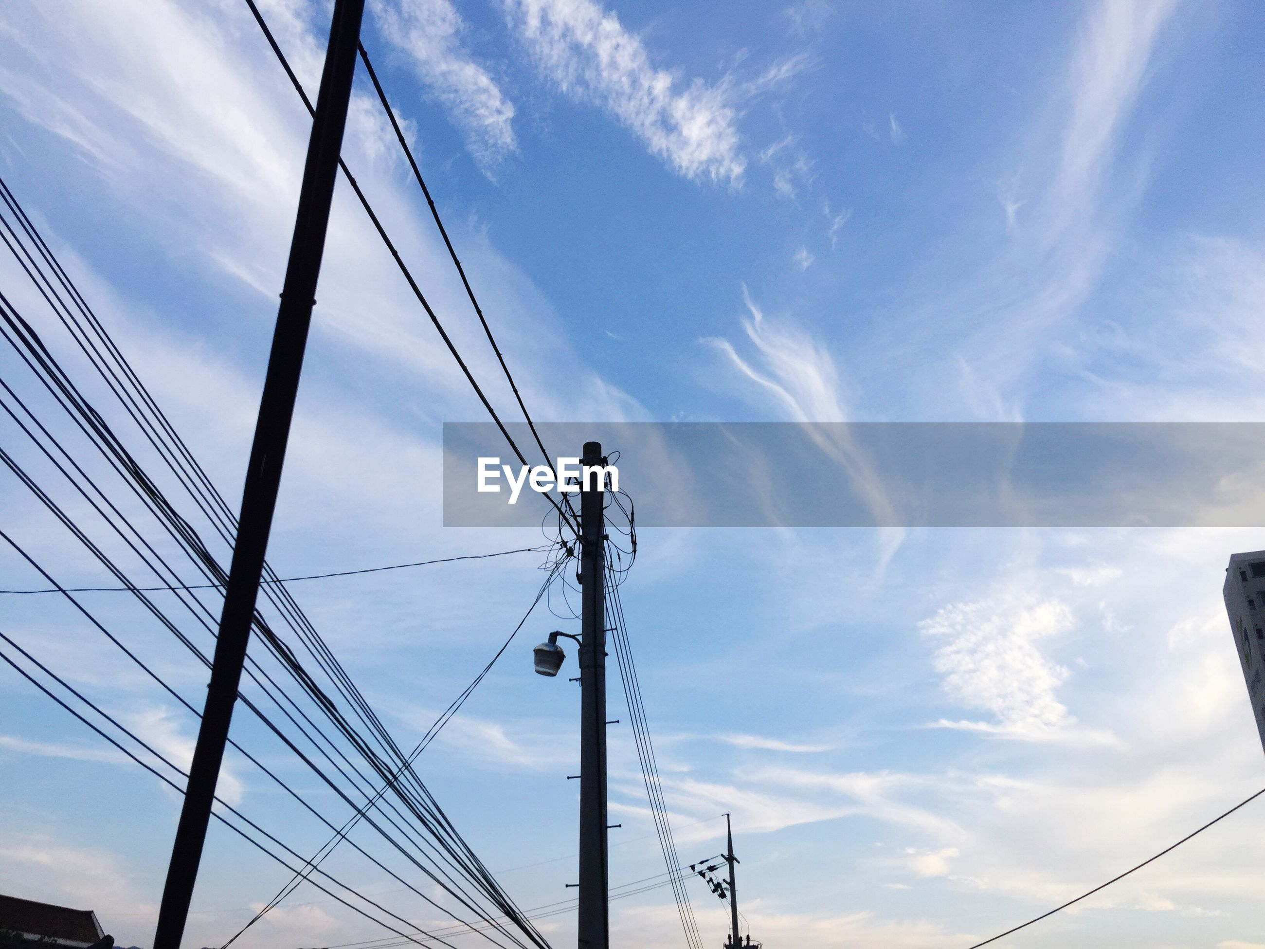 low angle view, connection, electricity, electricity pylon, sky, blue, cloud, development, day, power line, tall - high, power supply, outdoors, progress, high section, bright, back lit, no people, tall, cloud - sky