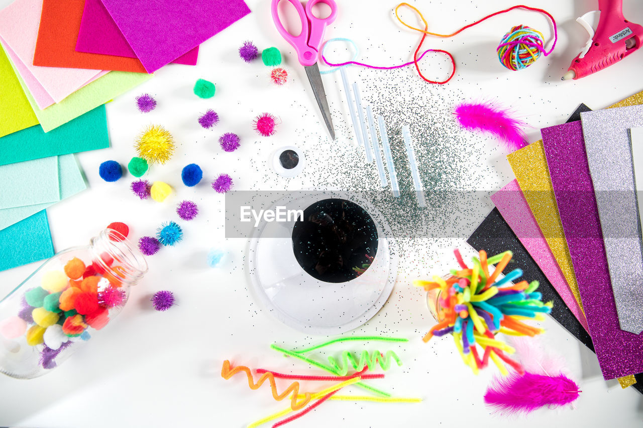 multi colored, art and craft, indoors, high angle view, table, still life, paper, no people, creativity, craft, close-up, choice, variation, directly above, large group of objects, watercolor paints, paint, decoration, ribbon, shape, art and craft equipment