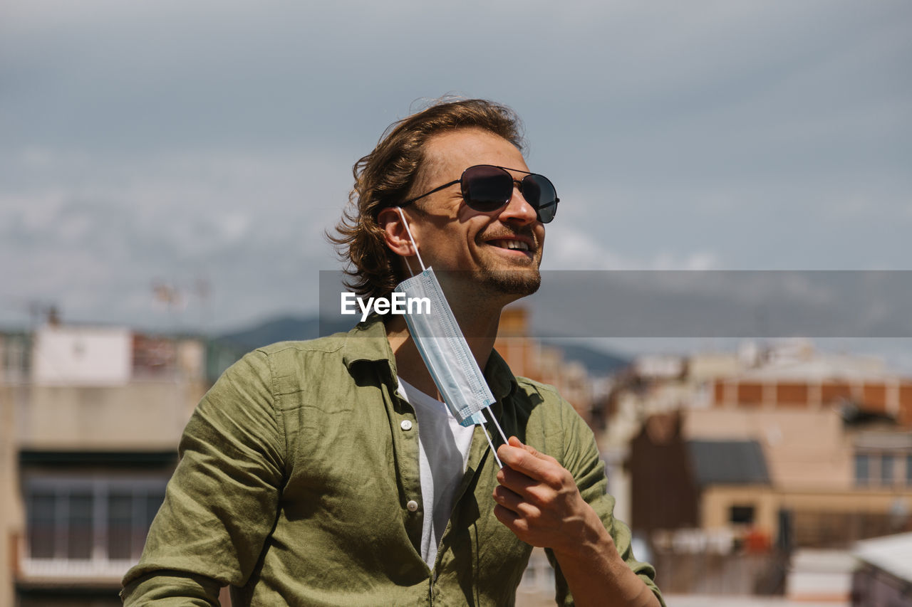 Handsome man in sunglasses joyfully removes the medical mask from his face on sunny day, outdoor.