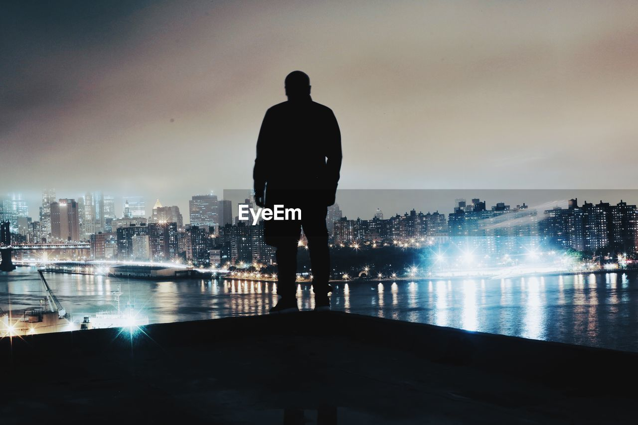 Rear View Of Silhouette Of Man With Cityscape In Background