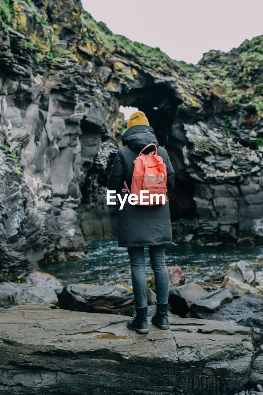 rock - object, real people, full length, rear view, one person, leisure activity, rock formation, casual clothing, backpack, nature, standing, lifestyles, outdoors, day, women, beauty in nature, adventure, waterfall, sky, people
