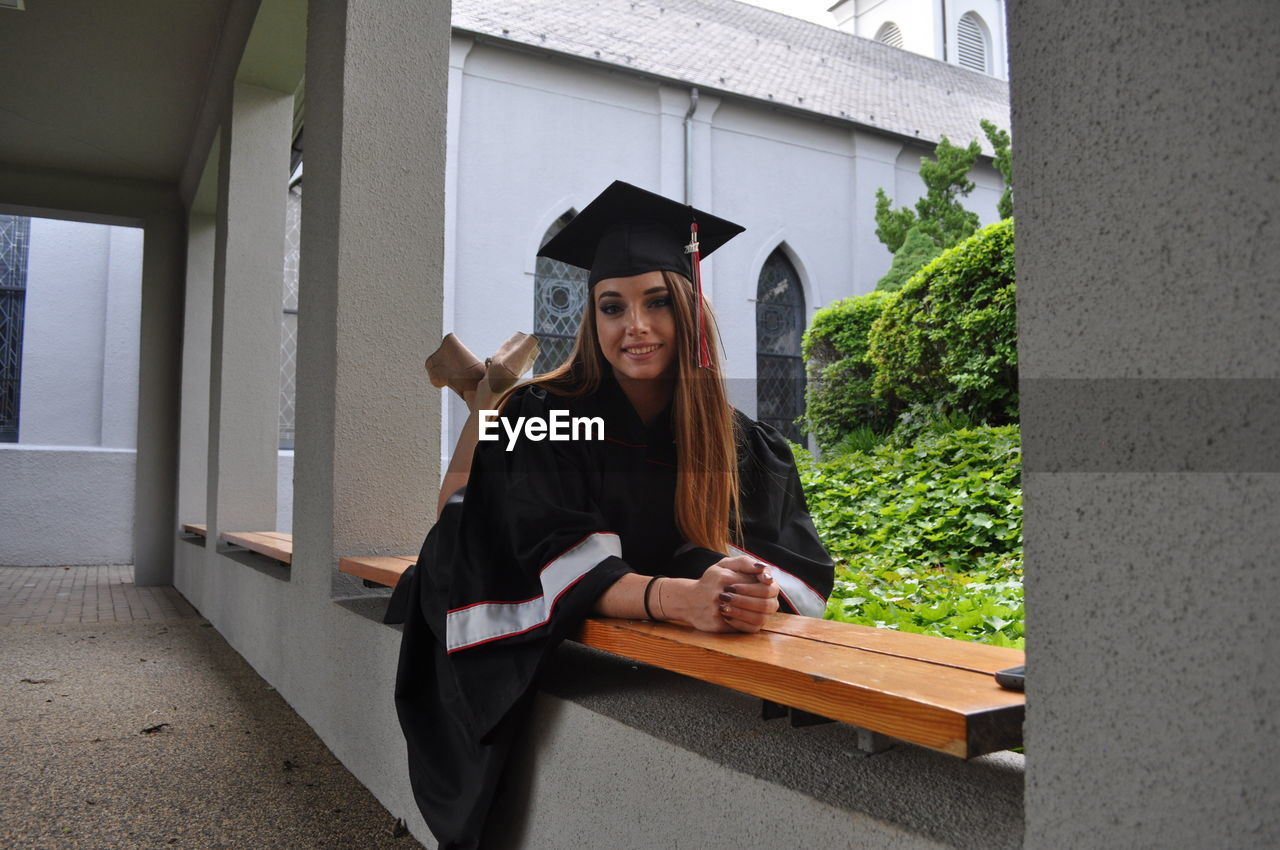 Portrait Of Smiling Female Graduate Lying Down On Bench In University