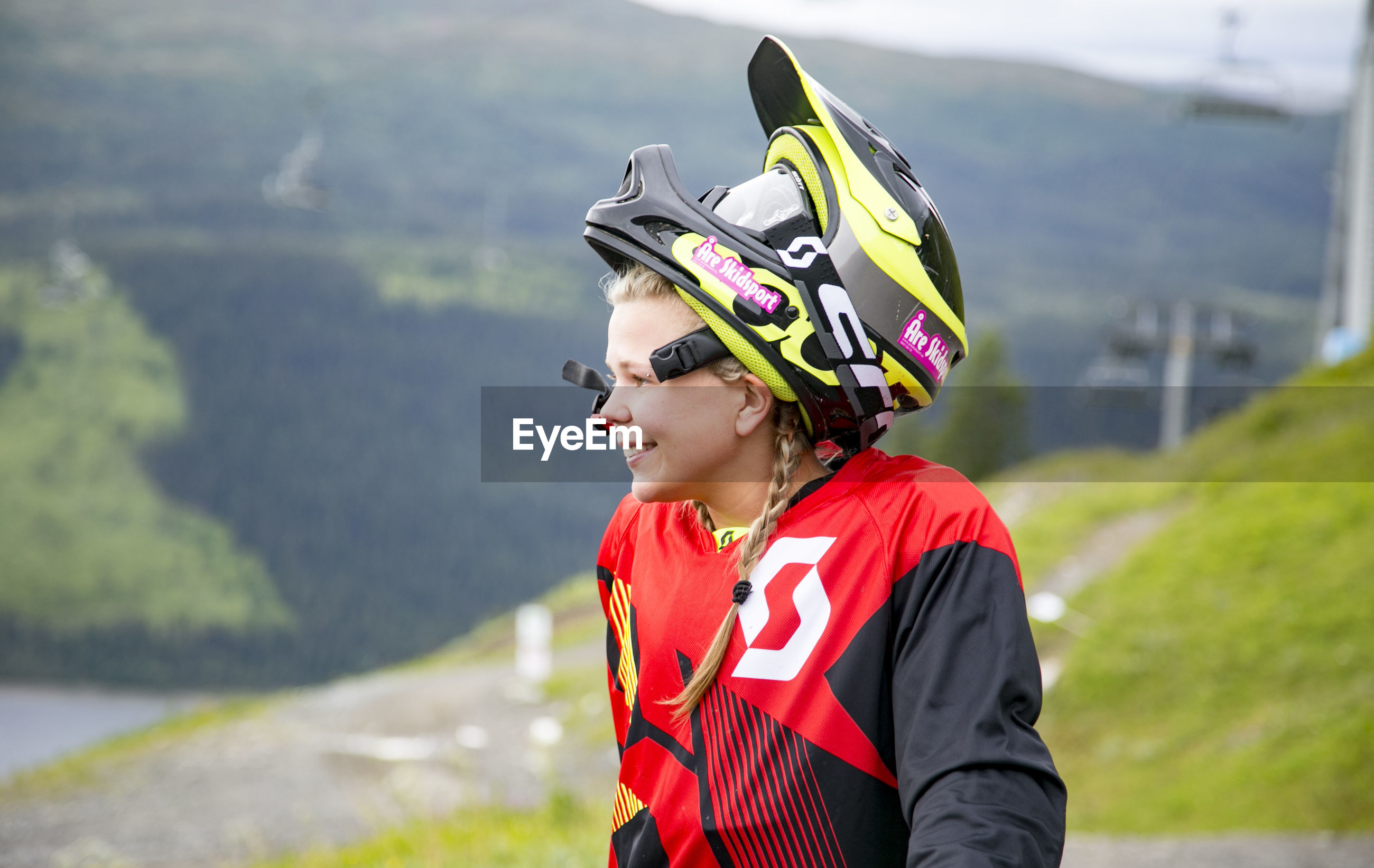 Young woman looking away while wearing crash helmet against mountain
