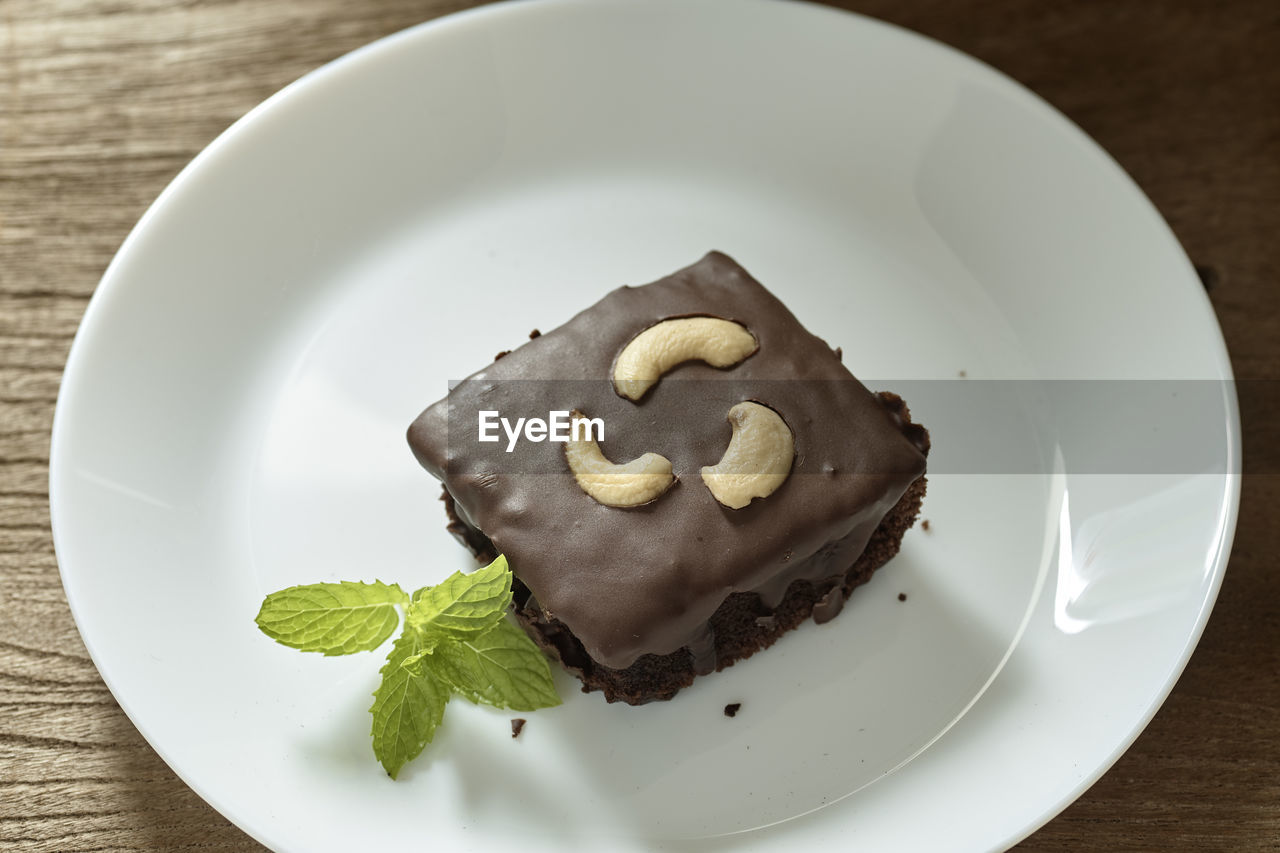 High angle view of chocolate cake slice in plate on table