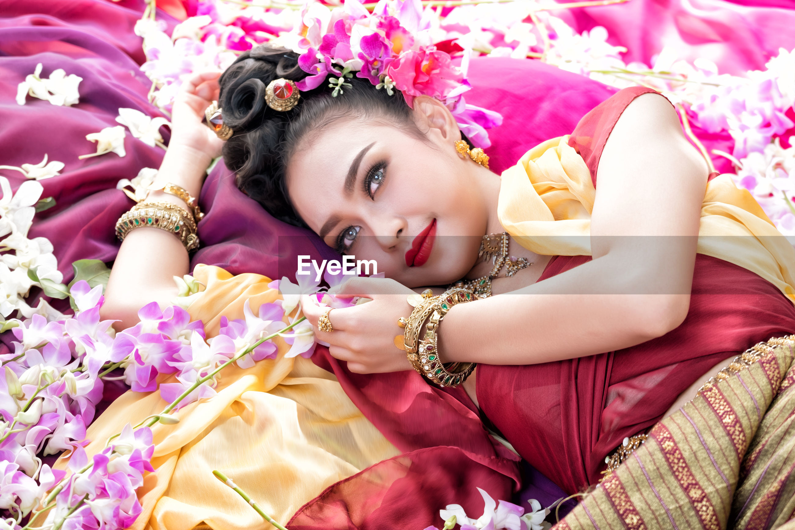High angle view of beautiful woman wearing traditional clothing and jewelry while lying with flowers on bed