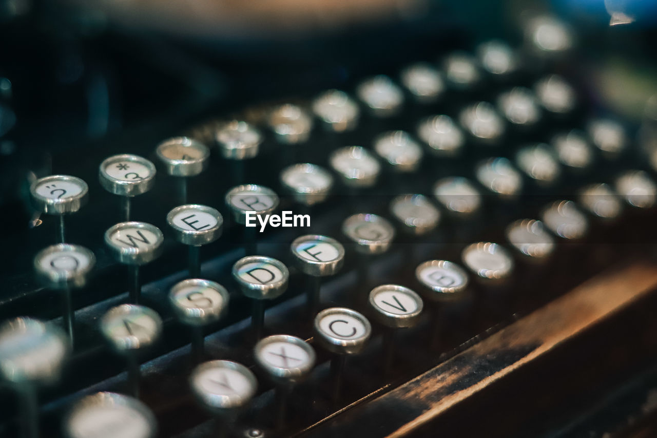 typewriter, technology, indoors, close-up, retro styled, no people, communication, selective focus, letter, text, alphabet, computer equipment, antique, high angle view, still life, machinery, computer part, keyboard, western script, computer key, push button