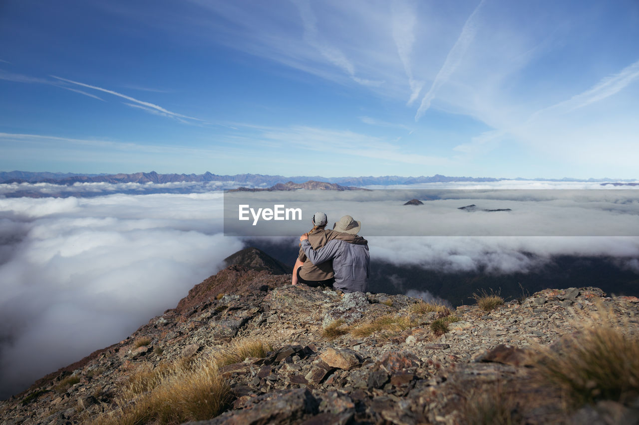 Rear view of man and woman sitting on rock against sky