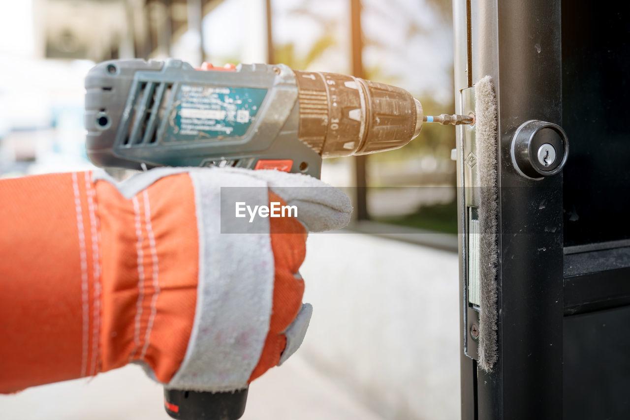 Close-up of hand drilling door