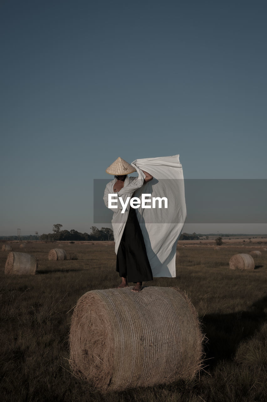 Rear view full length of young man holding fabric while standing on hay bale at agricultural landscape
