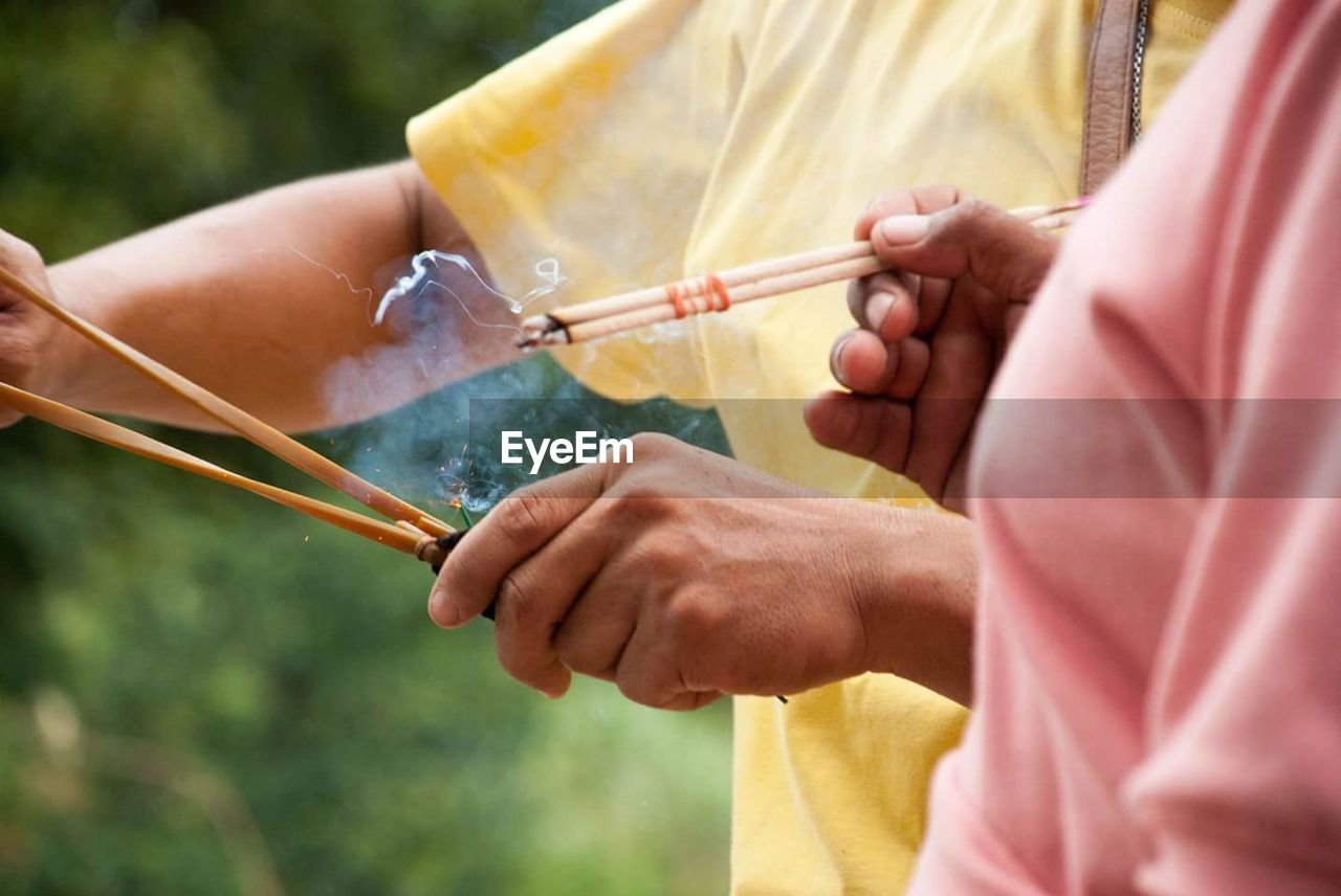 Midsection Of People Holding Incense Sticks