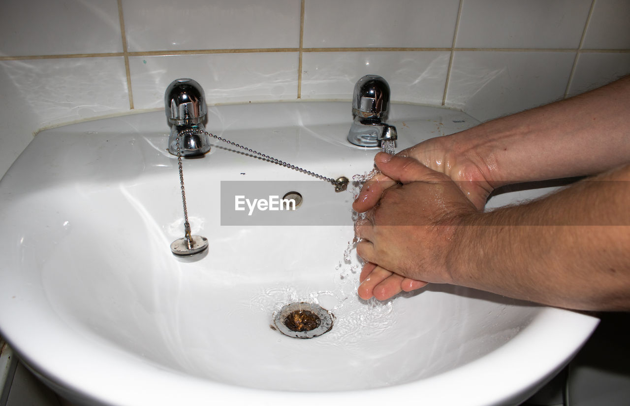 HIGH ANGLE VIEW OF WOMAN DRINKING WATER FROM FAUCET