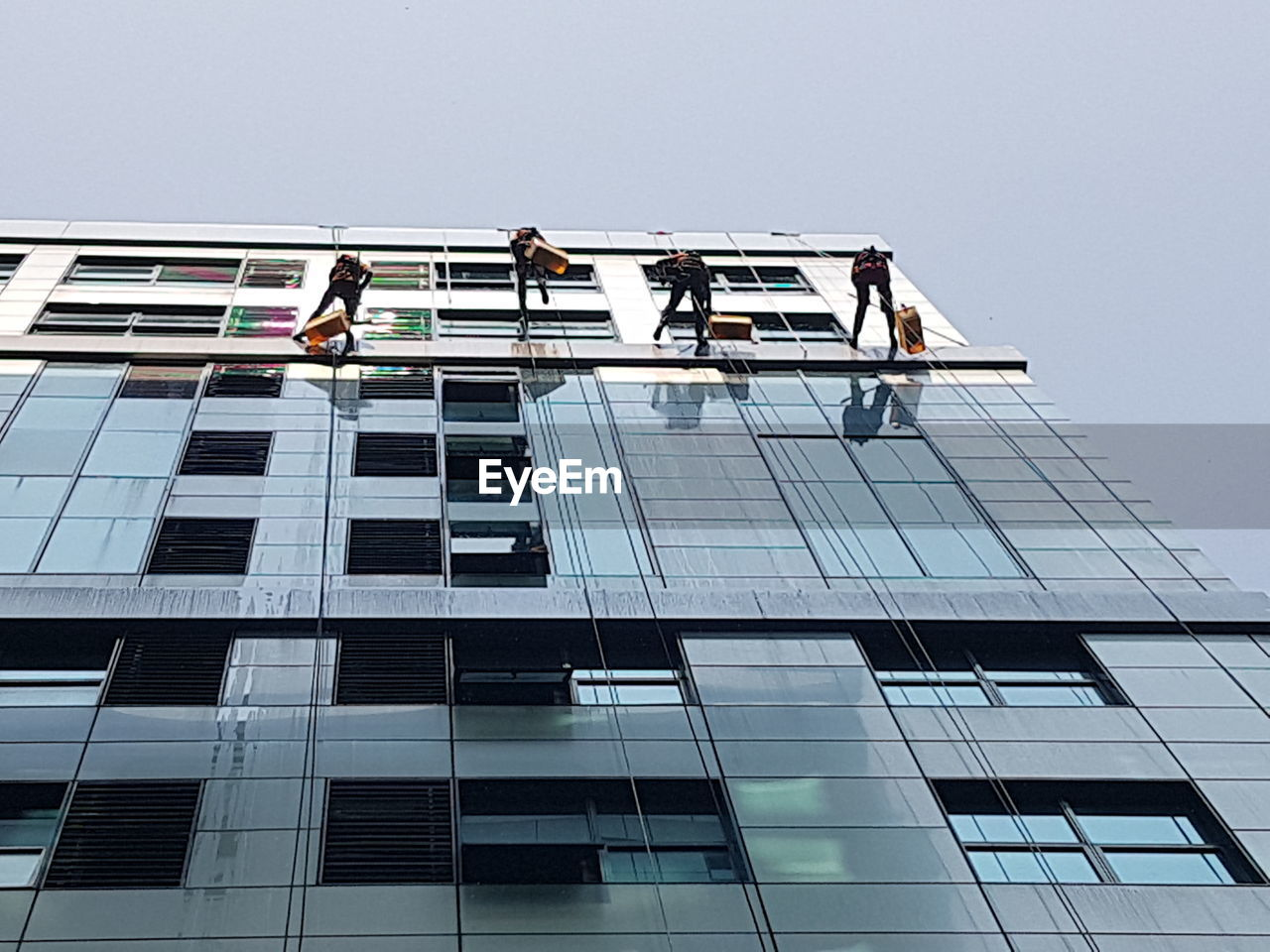 built structure, architecture, building exterior, building, low angle view, city, glass - material, sky, occupation, office building exterior, working, office, window washer, day, reflection, window, men, modern, people, outdoors, skyscraper, coworker