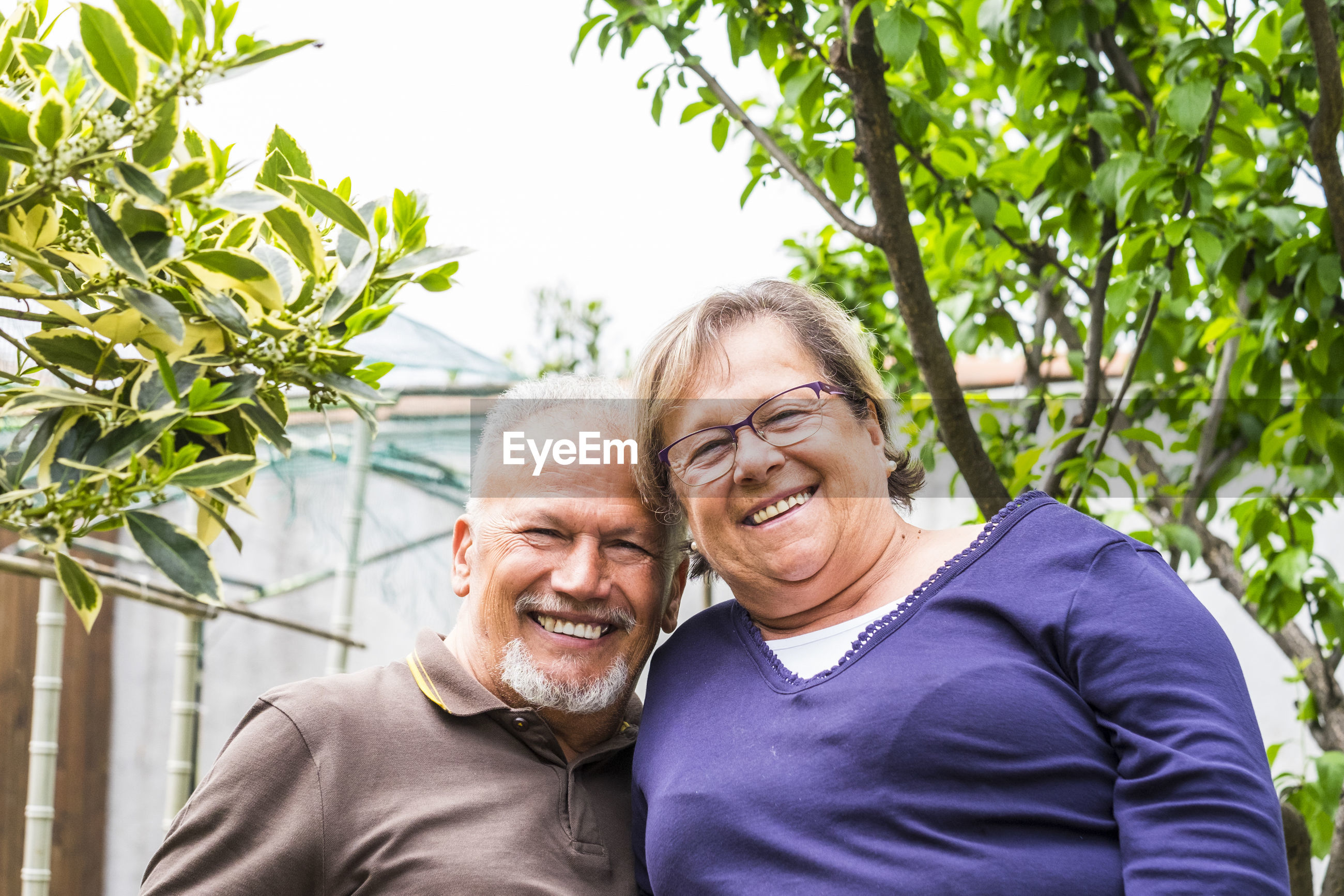Portrait of smiling man and woman standing by trees in yard