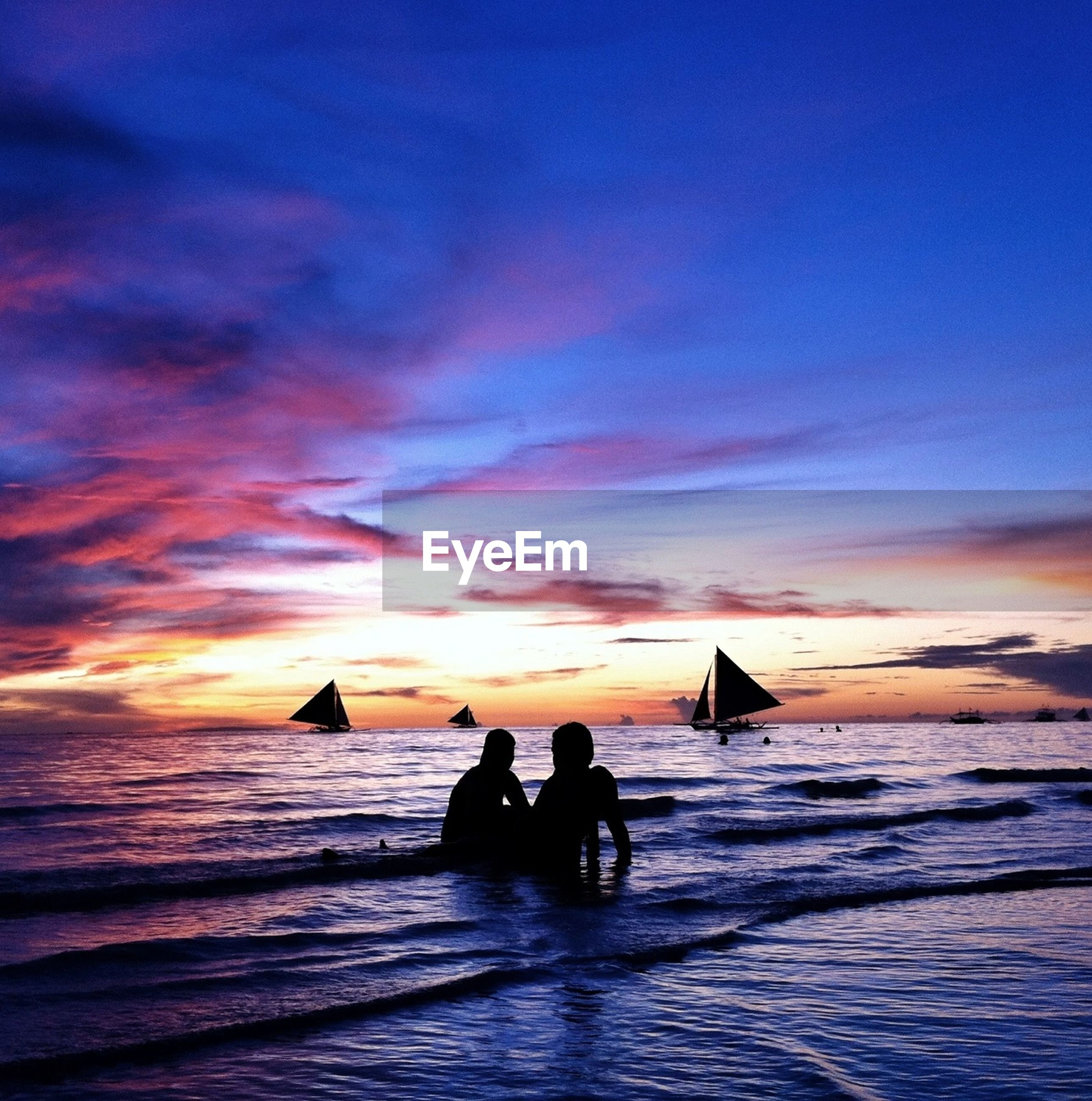 Silhouette couple relaxing at sea shore against sky during sunset