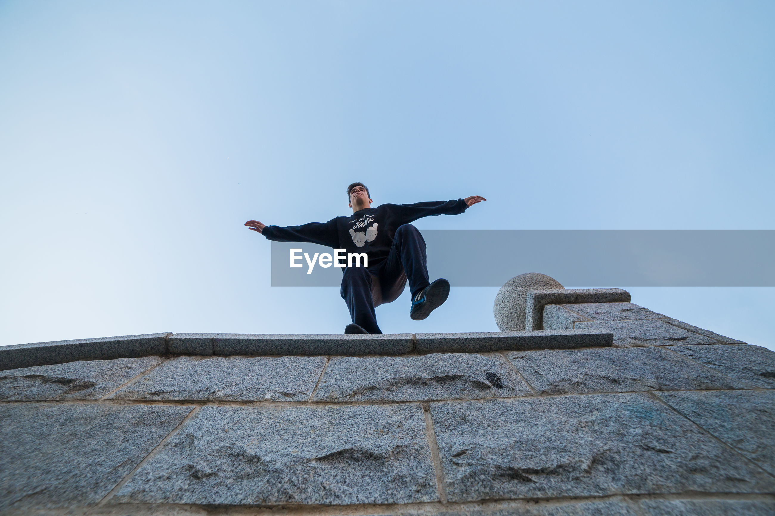 Low angle view of young man jumping from building against clear sky