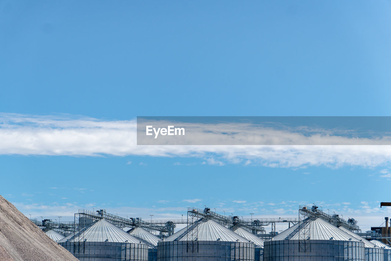 sky, architecture, built structure, cloud - sky, building exterior, blue, nature, day, no people, copy space, outdoors, building, industry, factory, city, roof, high section, connection, machinery, beauty in nature