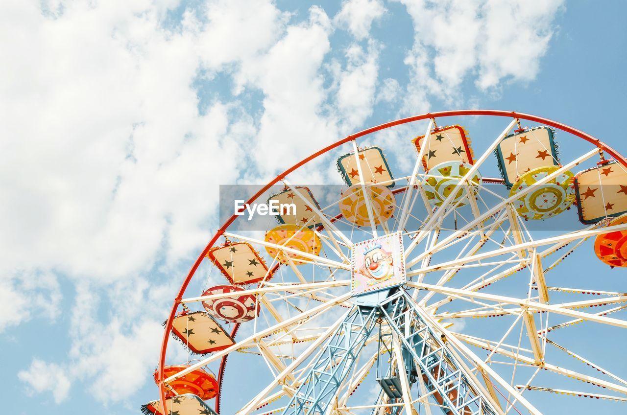 sky, amusement park, amusement park ride, ferris wheel, cloud - sky, arts culture and entertainment, low angle view, leisure activity, circle, shape, geometric shape, nature, fun, no people, day, carnival, outdoors, metal, blue, multi colored, fairground, wheel