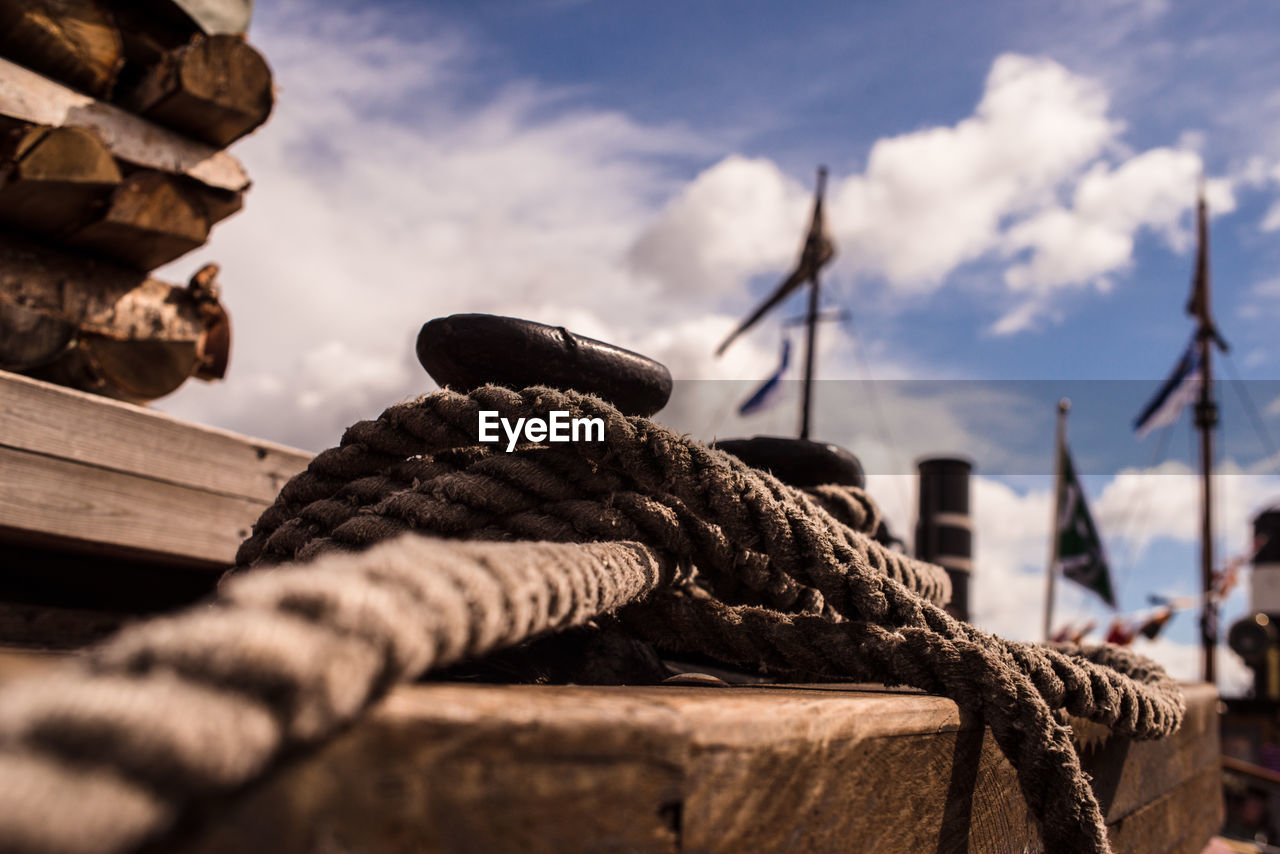 sky, focus on foreground, rope, close-up, no people, day, selective focus, wood - material, strength, cloud - sky, nature, nautical vessel, outdoors, transportation, stack, architecture, tied up, mode of transportation, metal, connection