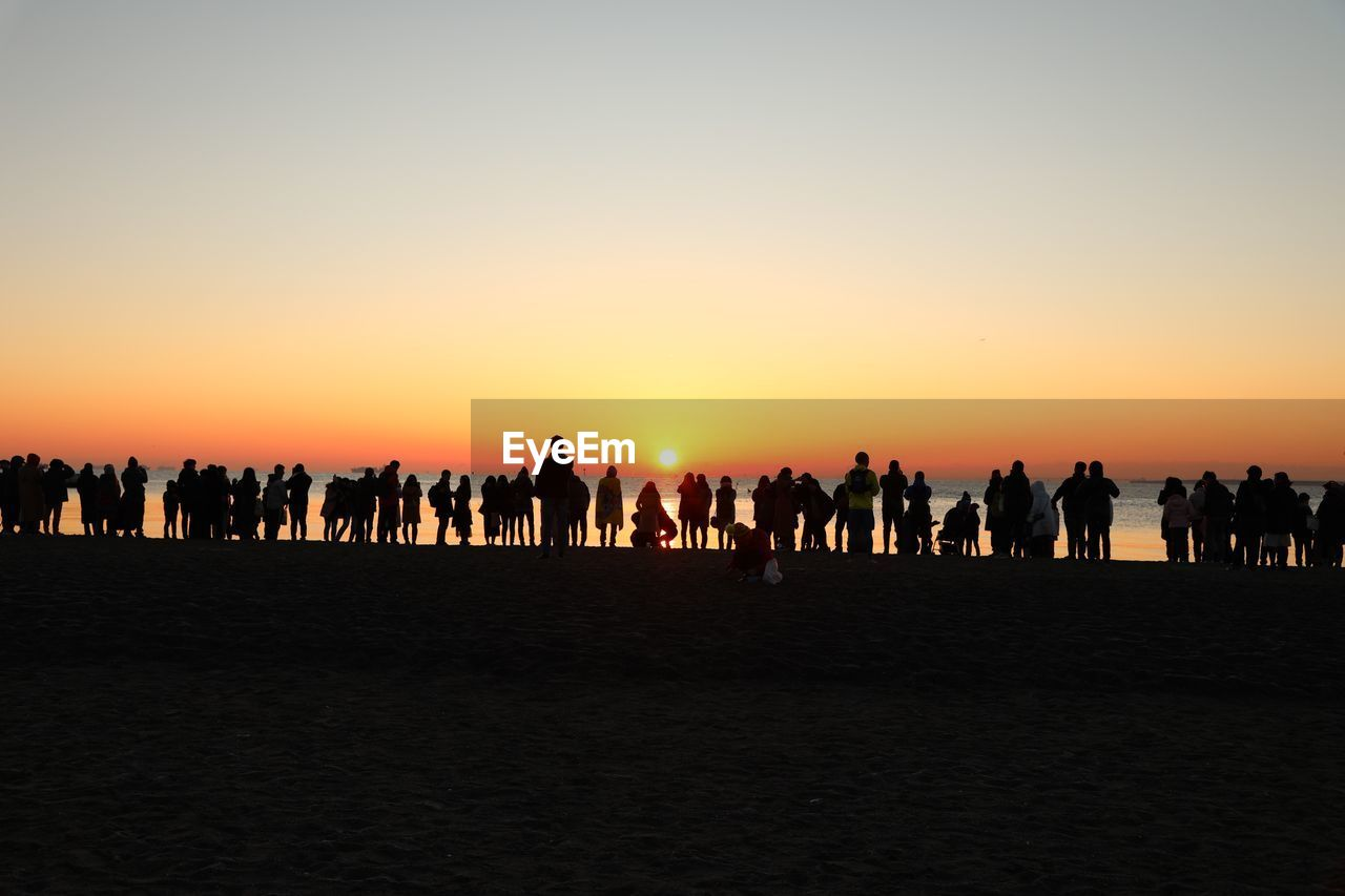 Silhouette people on beach against clear sky during sunset