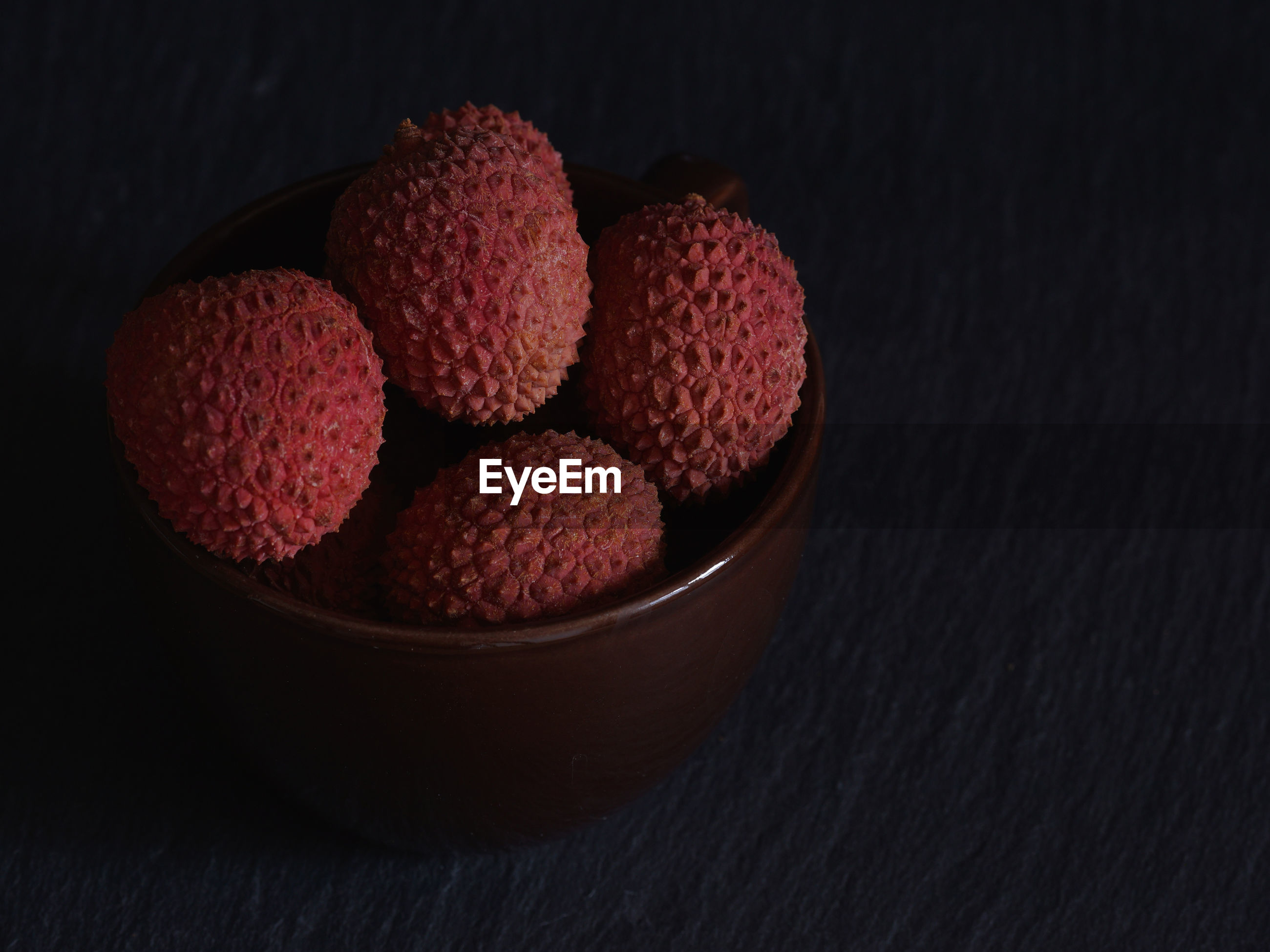 Close-up of lychees in bowl on black background