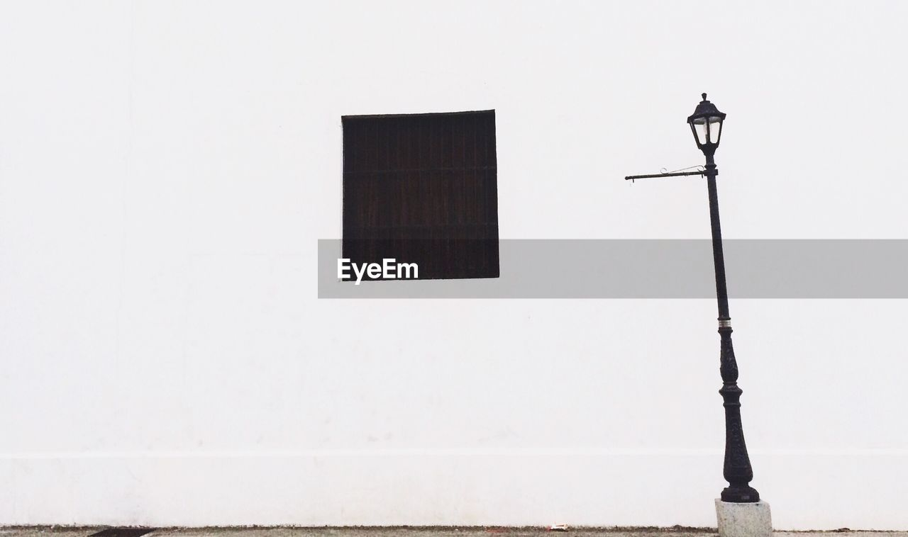 Low angle view of street light against house