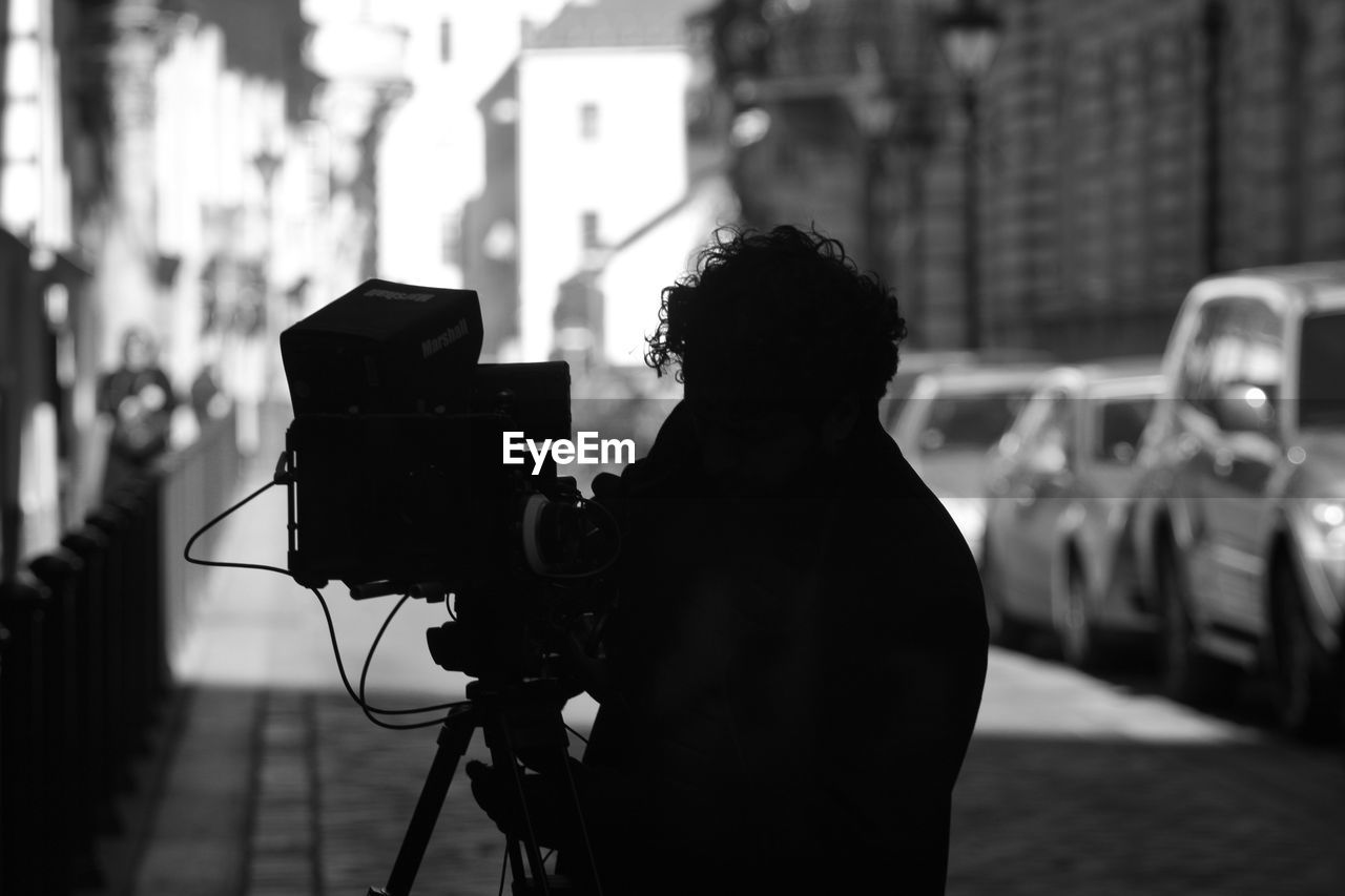 Silhouette Man Filming With Television Camera On Street