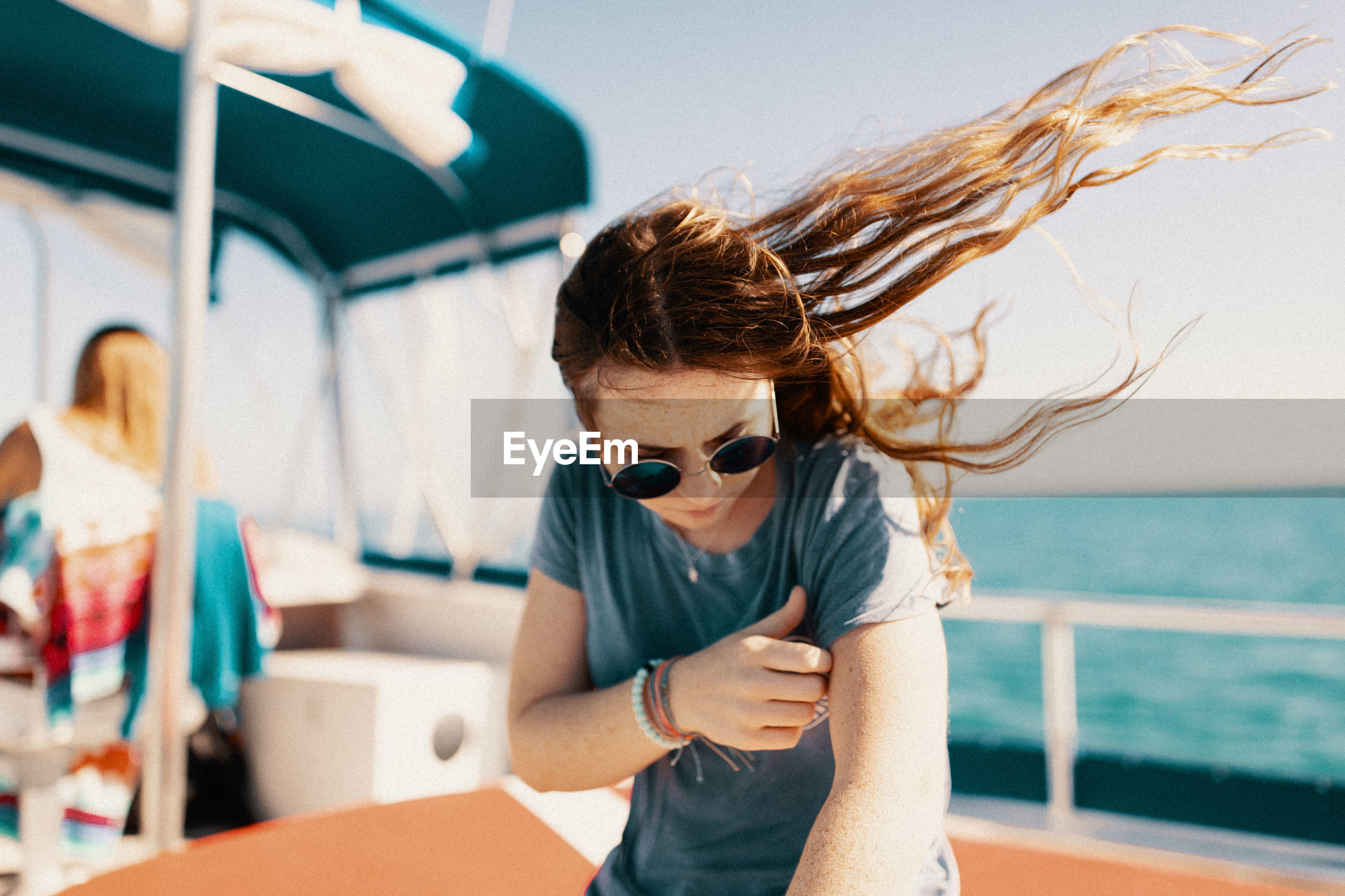 YOUNG WOMAN WEARING SUNGLASSES AGAINST SEA