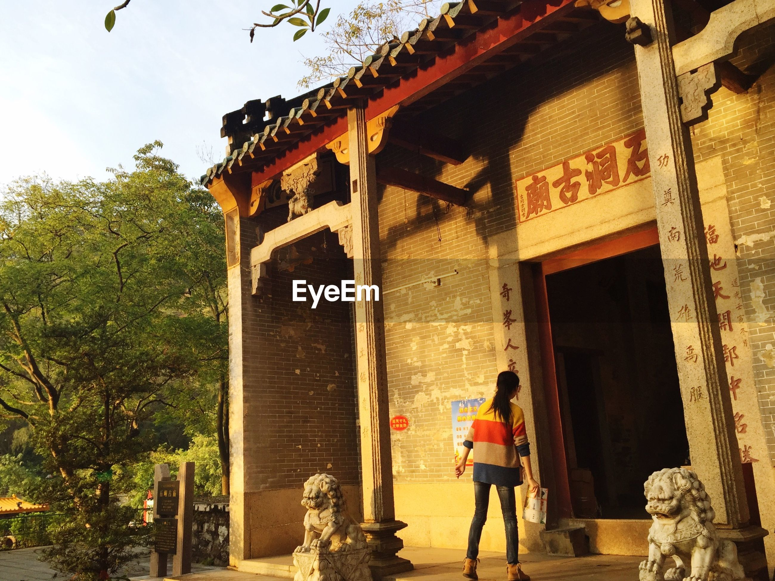 Woman standing near entrance of old temple against sky