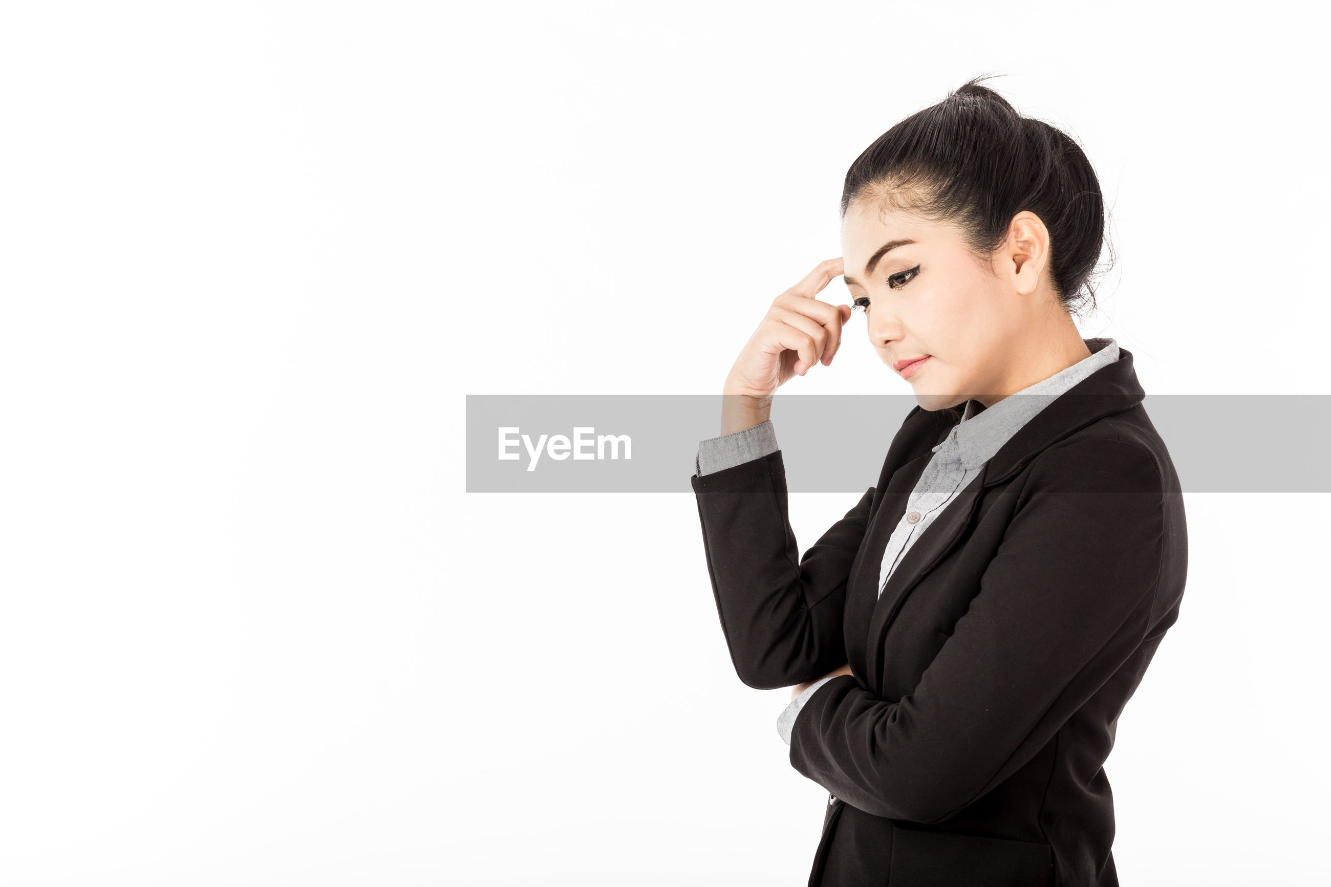Side view of thoughtful businesswoman standing against white background