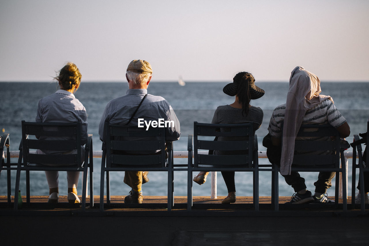 REAR VIEW OF PEOPLE SITTING ON CHAIR AT SEA SHORE