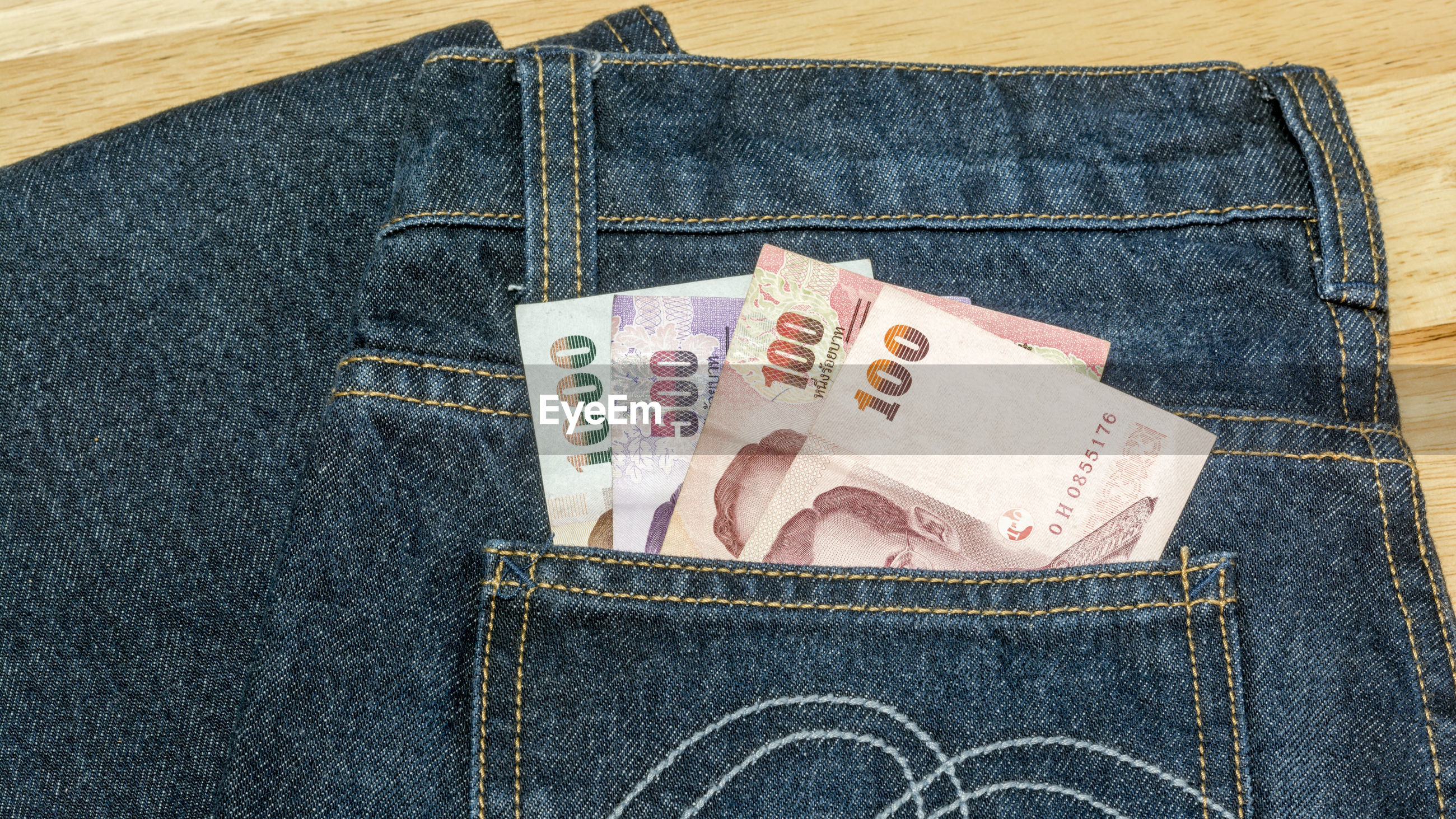Close-up of paper currency in jeans pocket