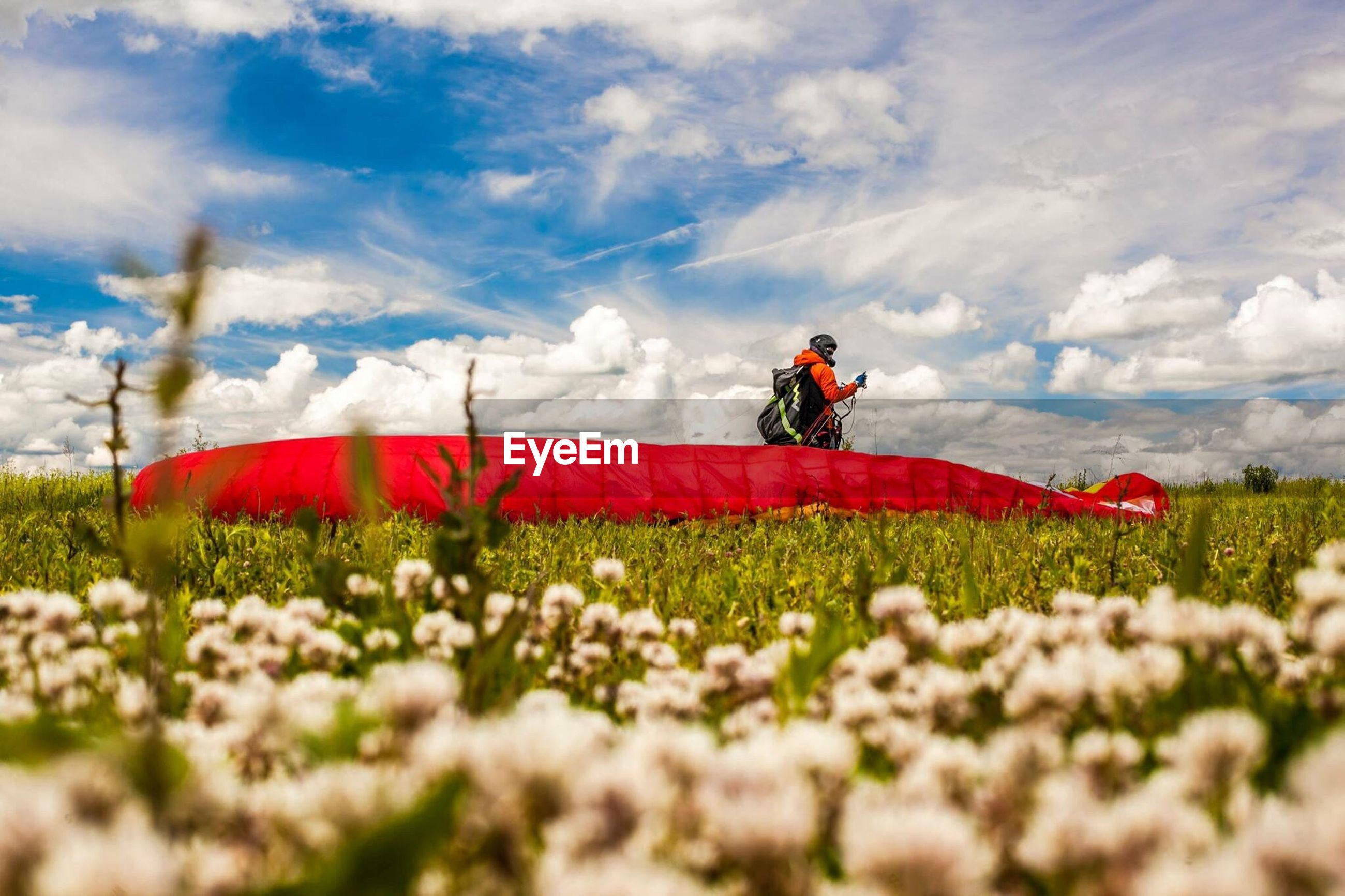 Person standing by parachute on field